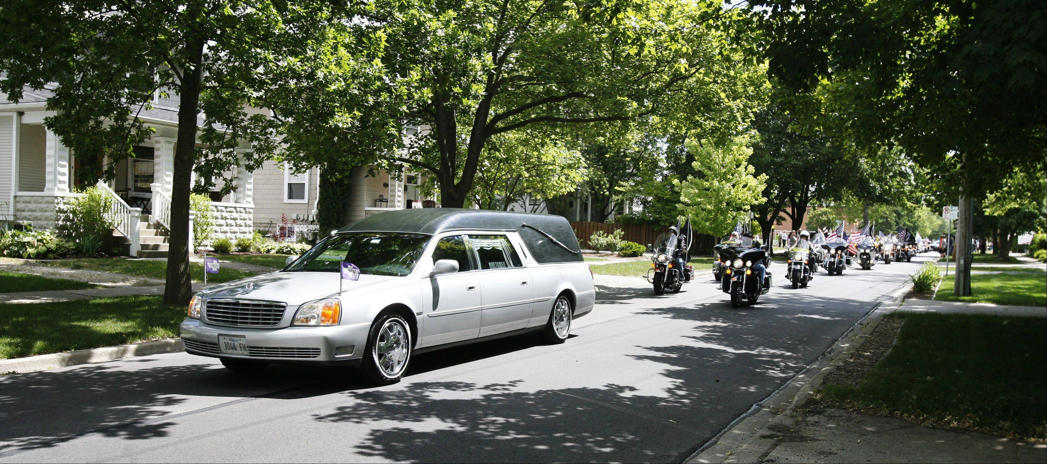 The body of Army Spc. Samuel Watts passes through downtown Wheaton on the way to the cemetery.