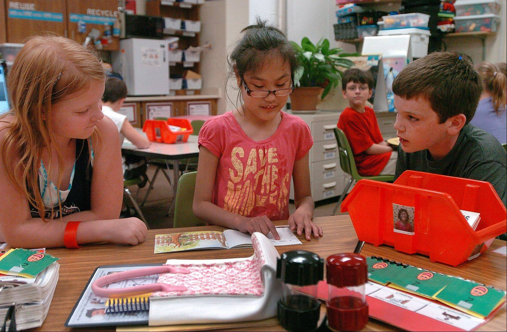 Third-grader Katrina Haman, left, and fourth-grader Patrick Kane, right, help fourth-grader Michid Mash-Ariun read during a program where students Stevenson Elementary School in Elk Grove Village read to their counterparts in special-needs classrooms.