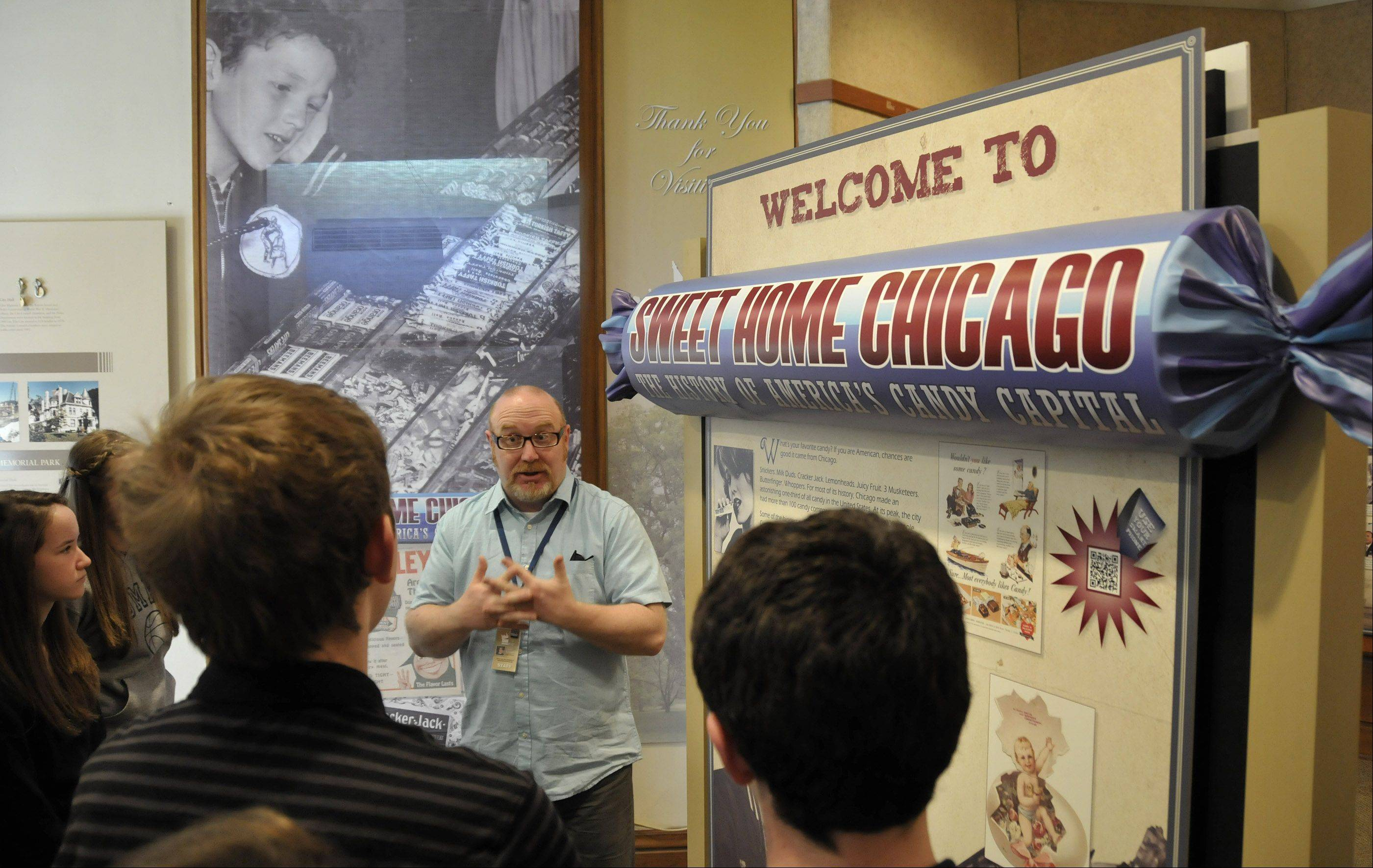 "Eighth-graders from St. Mary of Gostyn School in Downers Grove get an introduction to ""Sweet Home Chicago: The History of America's Candy Capital"" at the Elmhurst Historical Museum from museum curator Lance Tawzer."