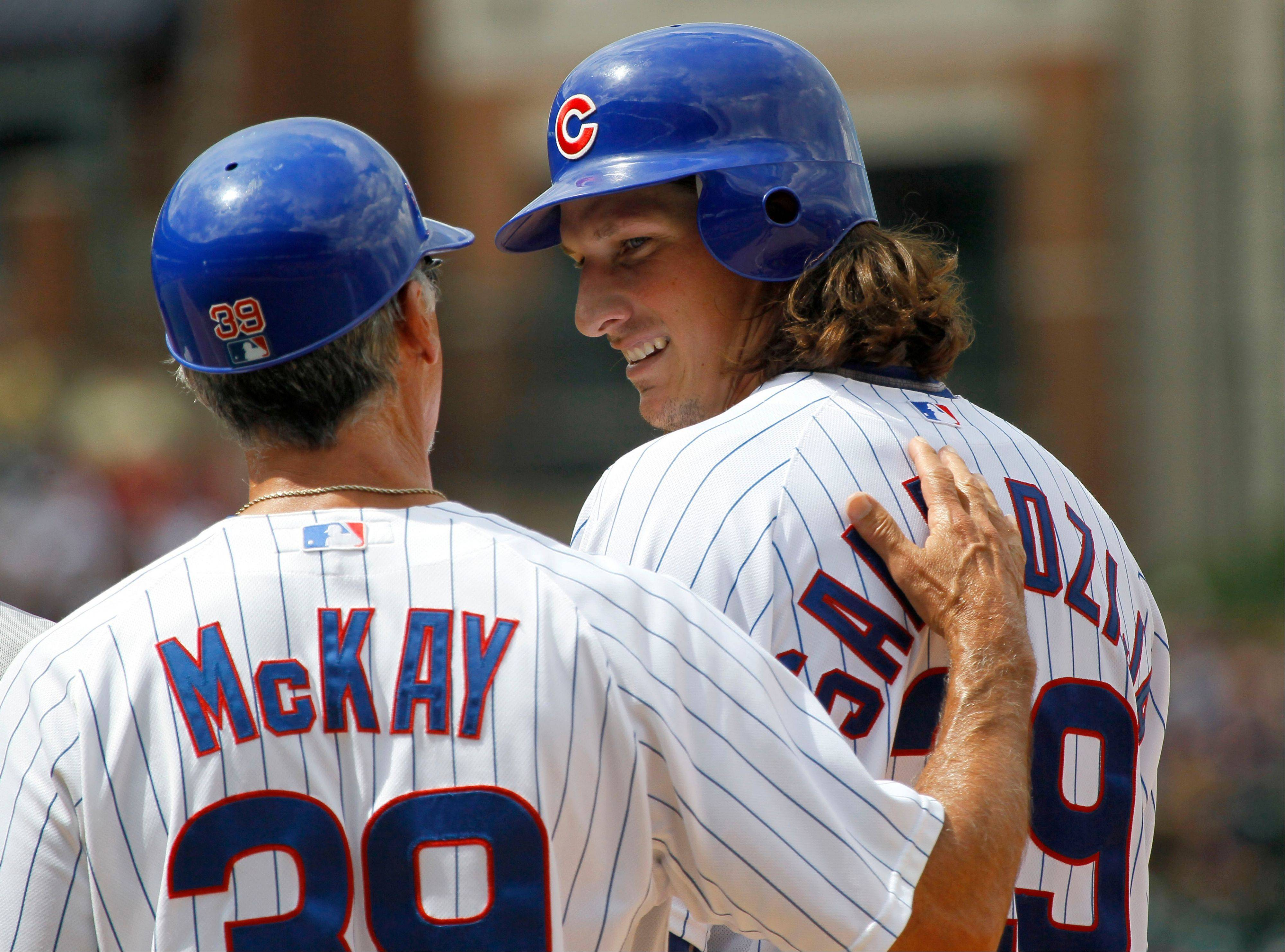 The Cubs' Jeff Samardzija smiles at first-base coach Dave McKay after his RBI single in the fifth inning Tuesday at Wrigley Field.