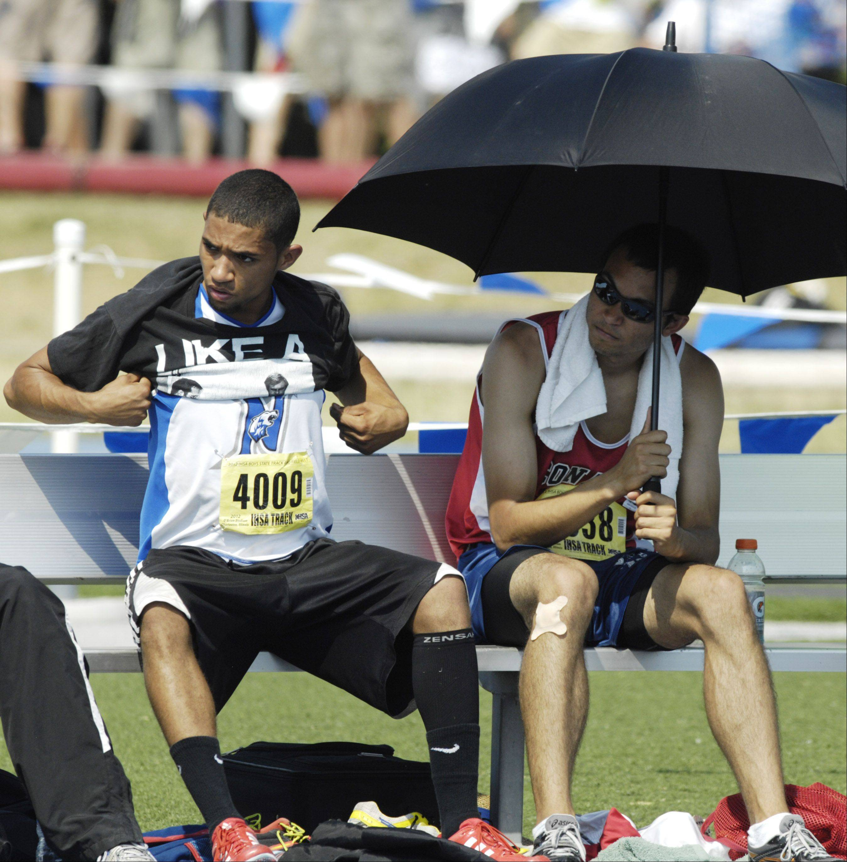 St. Charles North's Oshay Hodges sits next to Conant's Ben Bowers who is shading himself with an umbrella Saturday.