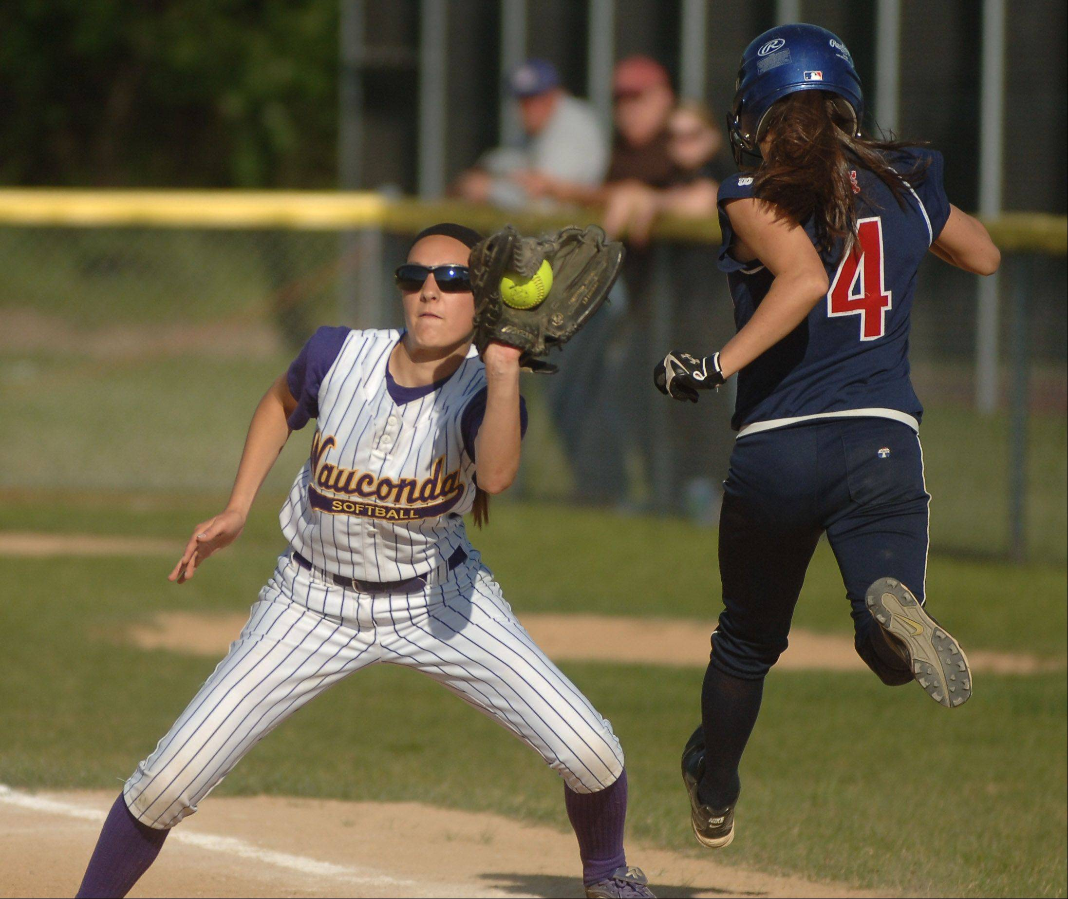 St. Viator's Colleen Dunne, 4, makes it safely to first base ahead of the throw to Wauconda's Megan Grobelny during Monday's regional softball game in Wauconda.