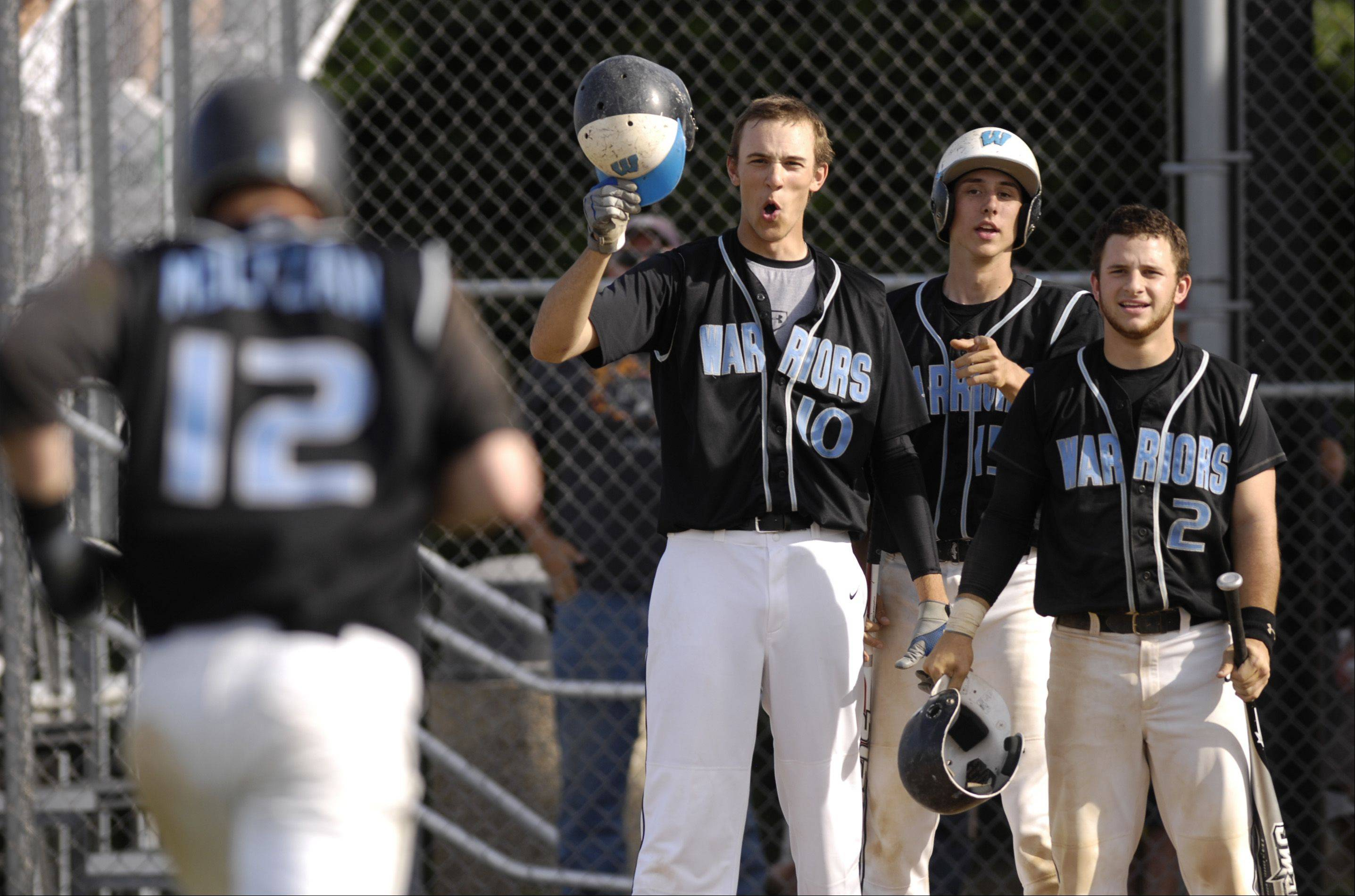 Willowbrook's Cal Moltzan is congratulated by teammates Mike Rothmund, Tom Van Kooten, and Kurt Gitchell following his home run against Wheaton North in Wednesday's regional baseball action in Wheaton.