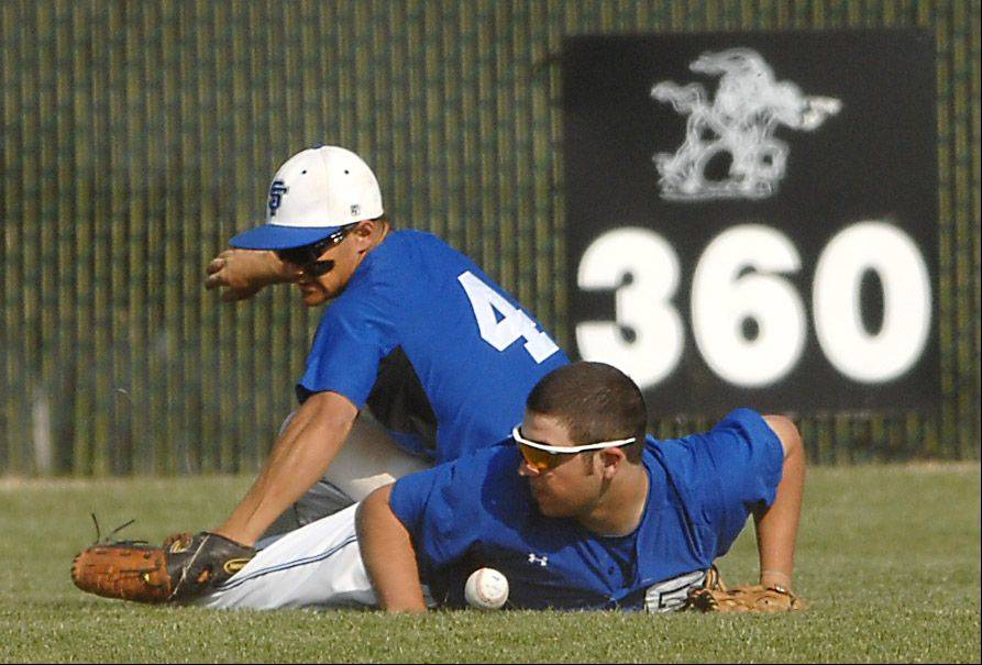 St. Francis' Alex Alcantar rolls over center fielder Jack Petrando after colliding during Thursday's baseball game in Maple Park.