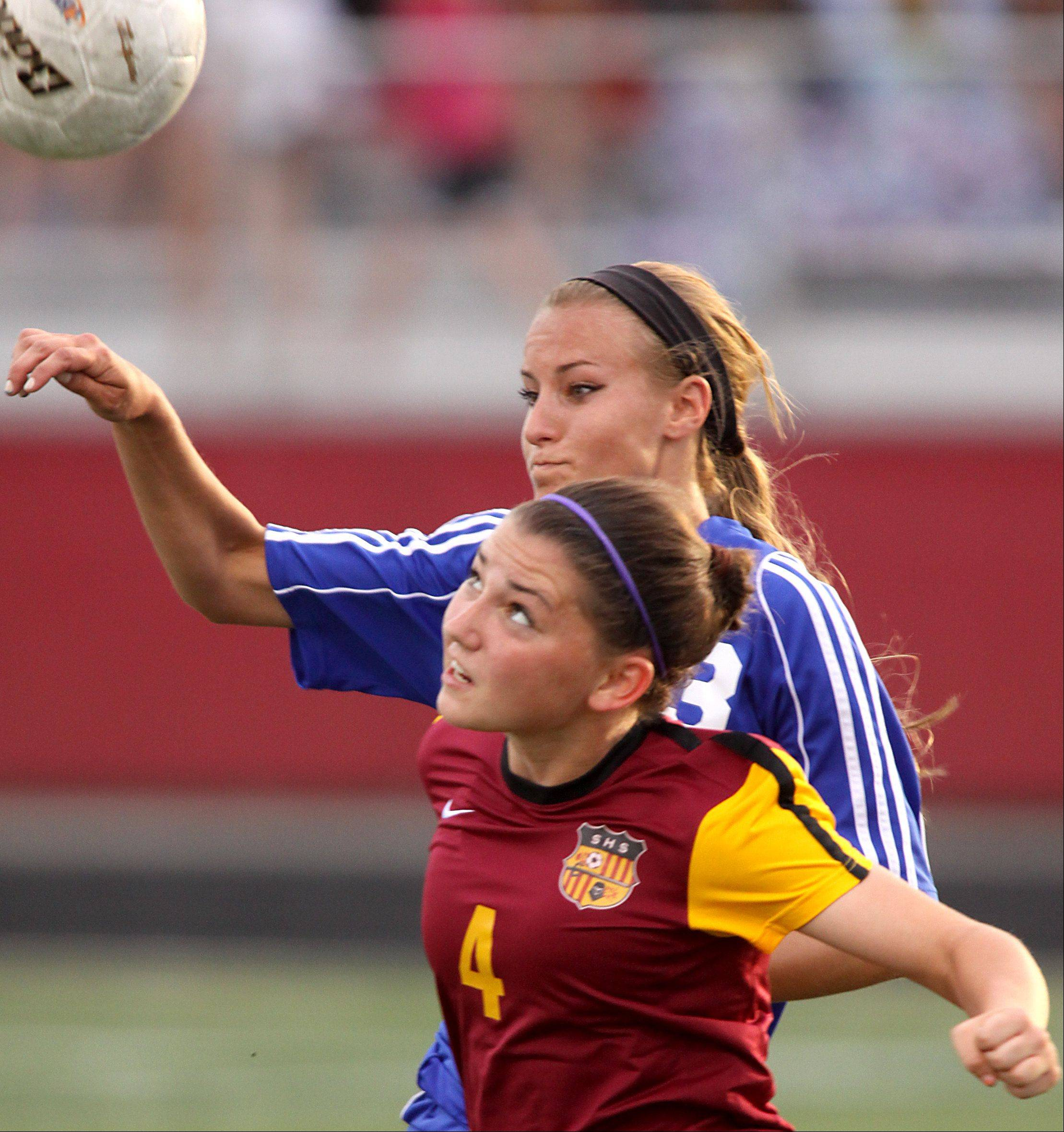Schaumburg's Amanda Kelly, front, and St. Charles North's Lauren Koehl battle for control of the ball during Friday's sectional title soccer game in Schaumburg.