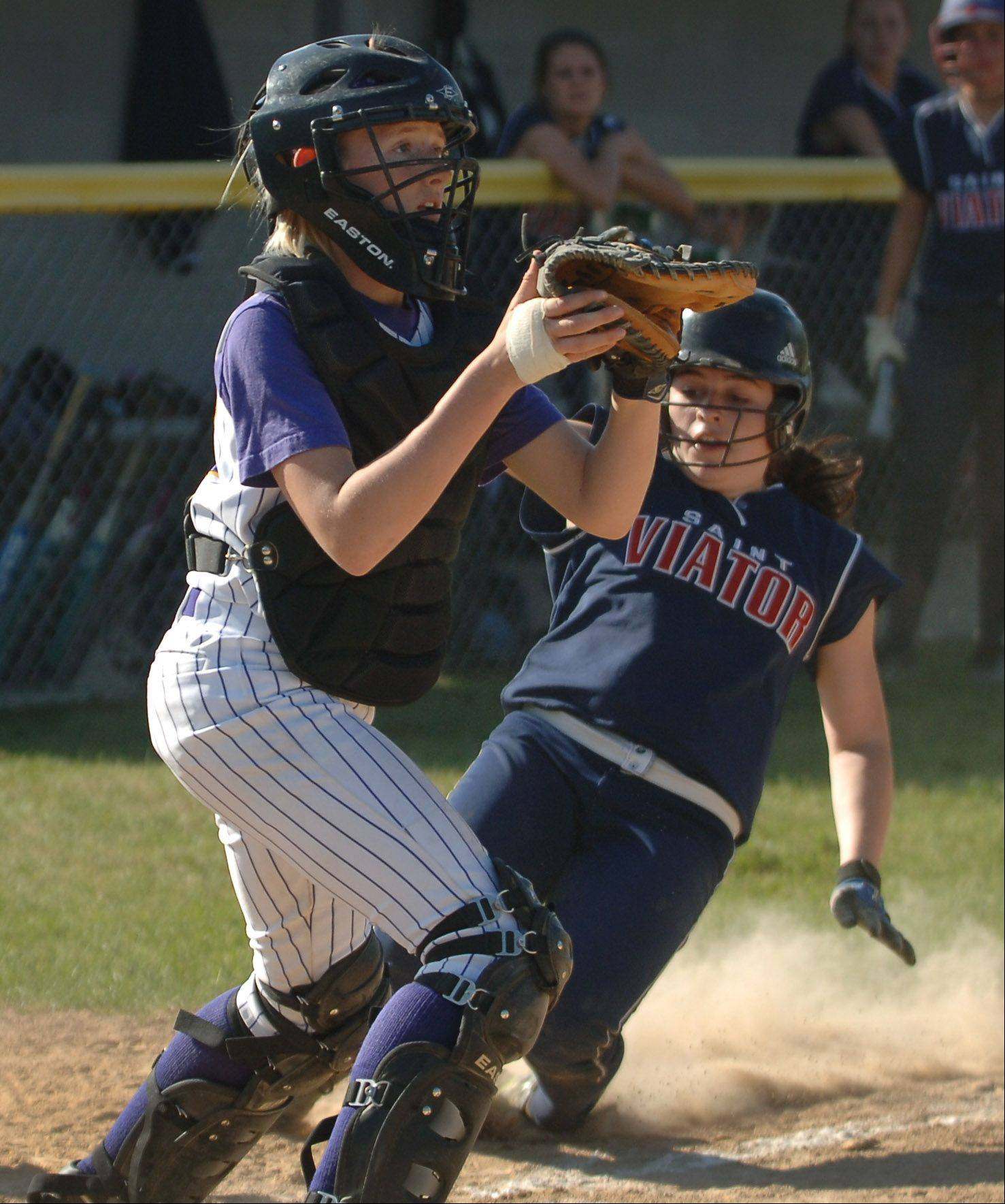 Wauconda catcher Paige Motley, left, waits for the throw as St. Viator's Lauren Prazuch slides safely into home during Monday's regional softball game in Wauconda.