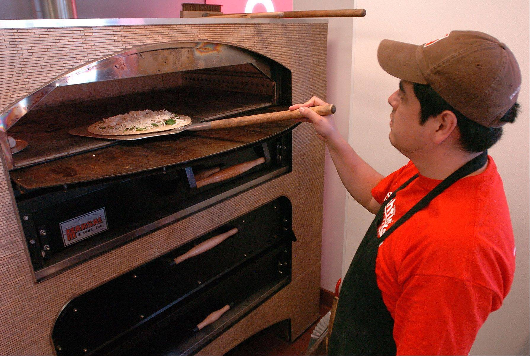 Adrian Andrade puts a no-carb white pizza in the oven at Eshticken in Hoffman Estates.
