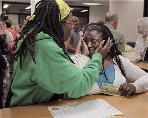 In this June 1, 2011 file photo, Janean Watkins, left, and Lakeesha Harris embrace after being the first in line to obtain a civil union license from the Cook County Office of Vital Records in Chicago. They are among more than two dozen same-sex couples filing lawsuits Wednesday challenging the constitutionality of Illinois' marriage laws. Advocates for the American Civil Liberties Union of Illinois and Lambda Legal are each filing a lawsuit on behalf of the couples. Their goal is to make same-sex marriage legal.