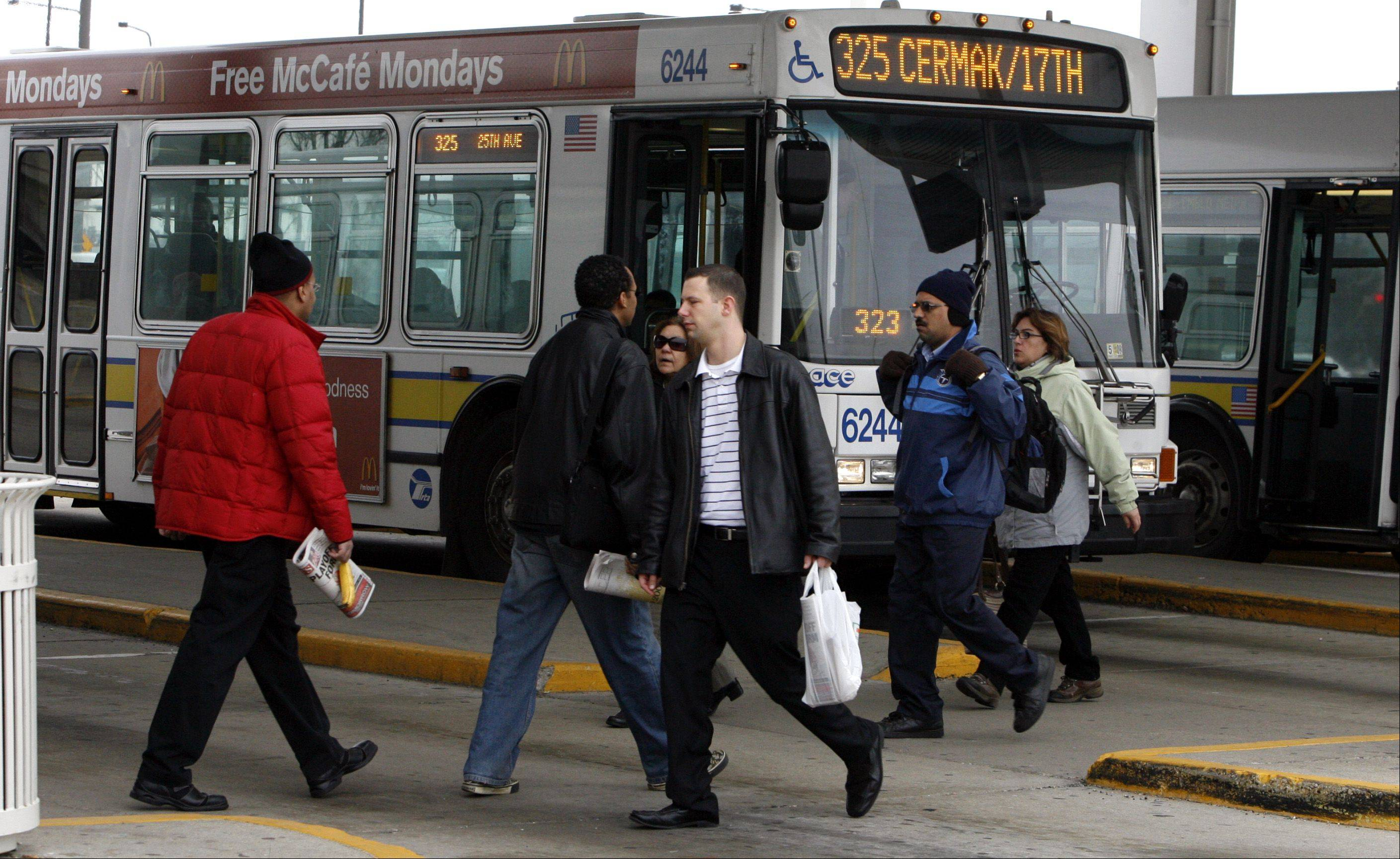 Commuters board a Pace bus at the Rosemont CTA station. The RTA wants the two agencies to coordinate service better.