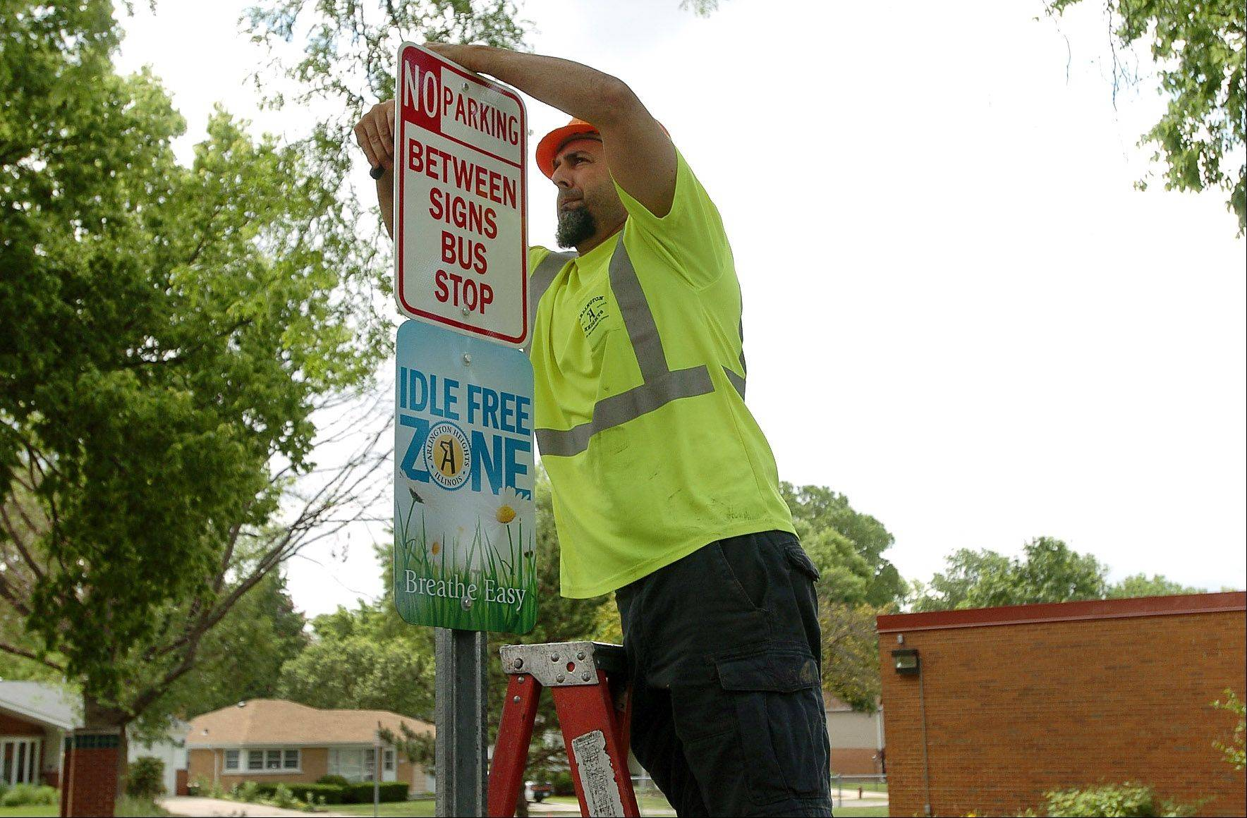Joe Wolfgram of the Arlington Heights Public Works Department installs Idle Free Zone and No Parking signs Wednesday in front of Westgate School. The signs are part of the village's newly launched Idle Free Arlington campaign.