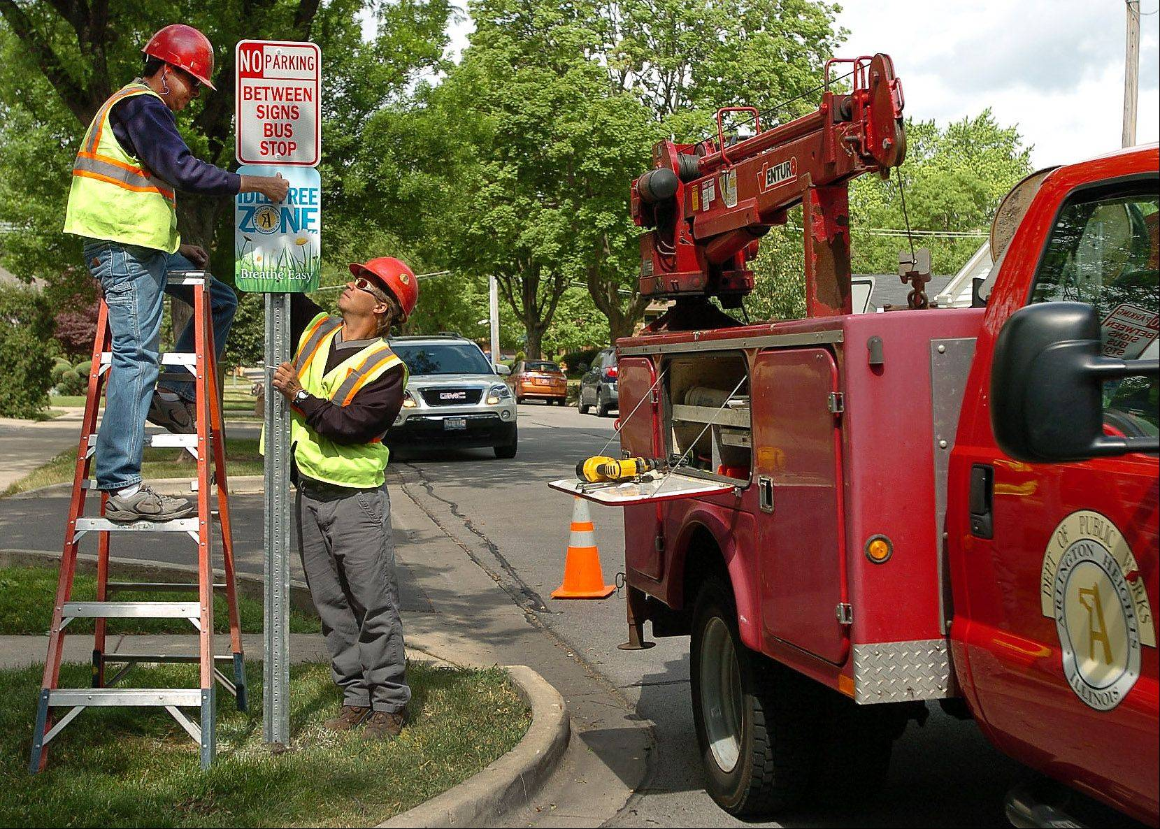 John Nolan, on the ladder, and Scott Bellanger, both crew members with the Arlington Heights Public Works Department, install Idle Free Zone and No Parking signs in front of Westgate School. The signs are part of the village's newly launched Idle Free Arlington campaign.