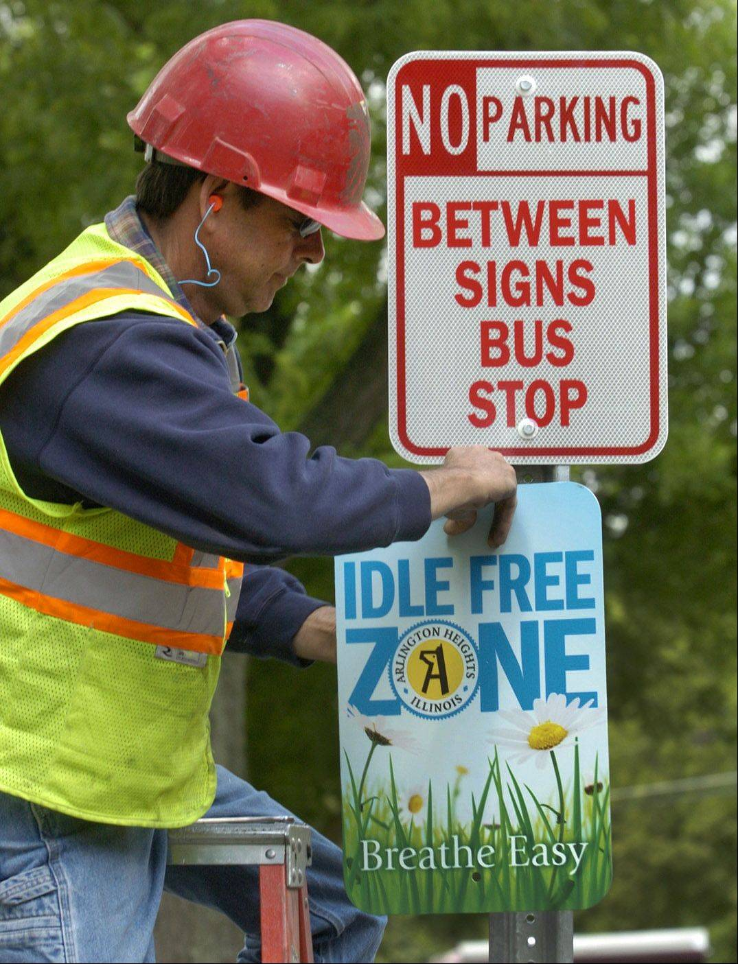 John Nolan, a crew member with the Arlington Heights Public Works Department, installs Idle Free Zone and No Parking signs in front of Westgate School. The signs are part of the village's newly launched Idle Free Arlington campaign.