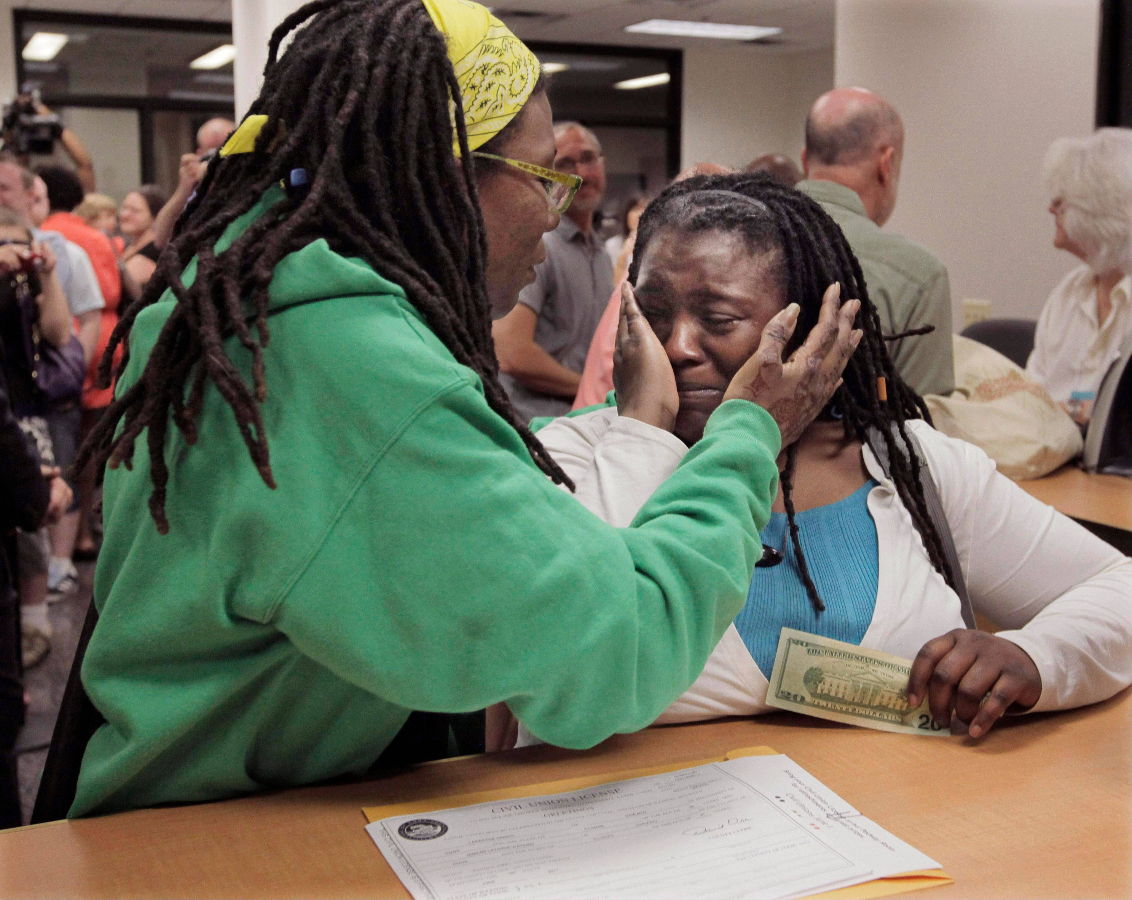 ASSOCIATED PRESSIn this June 1, 2011, file photo, Janean Watkins, left, and Lakeesha Harris embrace after being the first in line to obtain a civil union license from the Cook County Office of Vital Records in Chicago. They are among more than two dozen same-sex couples who filed lawsuits Wednesday, challenging the constitutionality of Illinois� marriage laws.