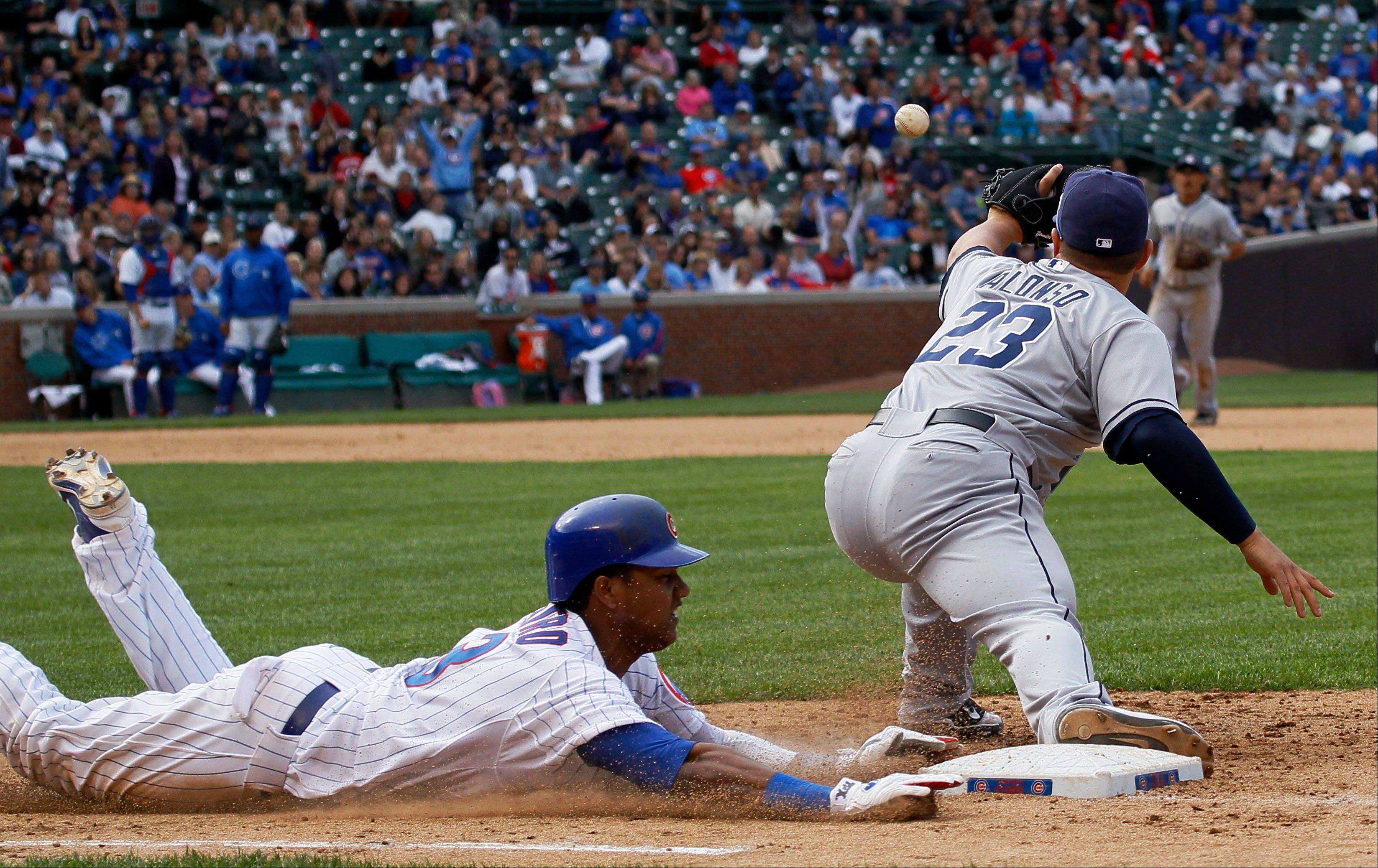 The Cubs' Starlin Castro, left, gets an infield RBI single with a headfirst slide into first base Wednesday at Wrigley Field.