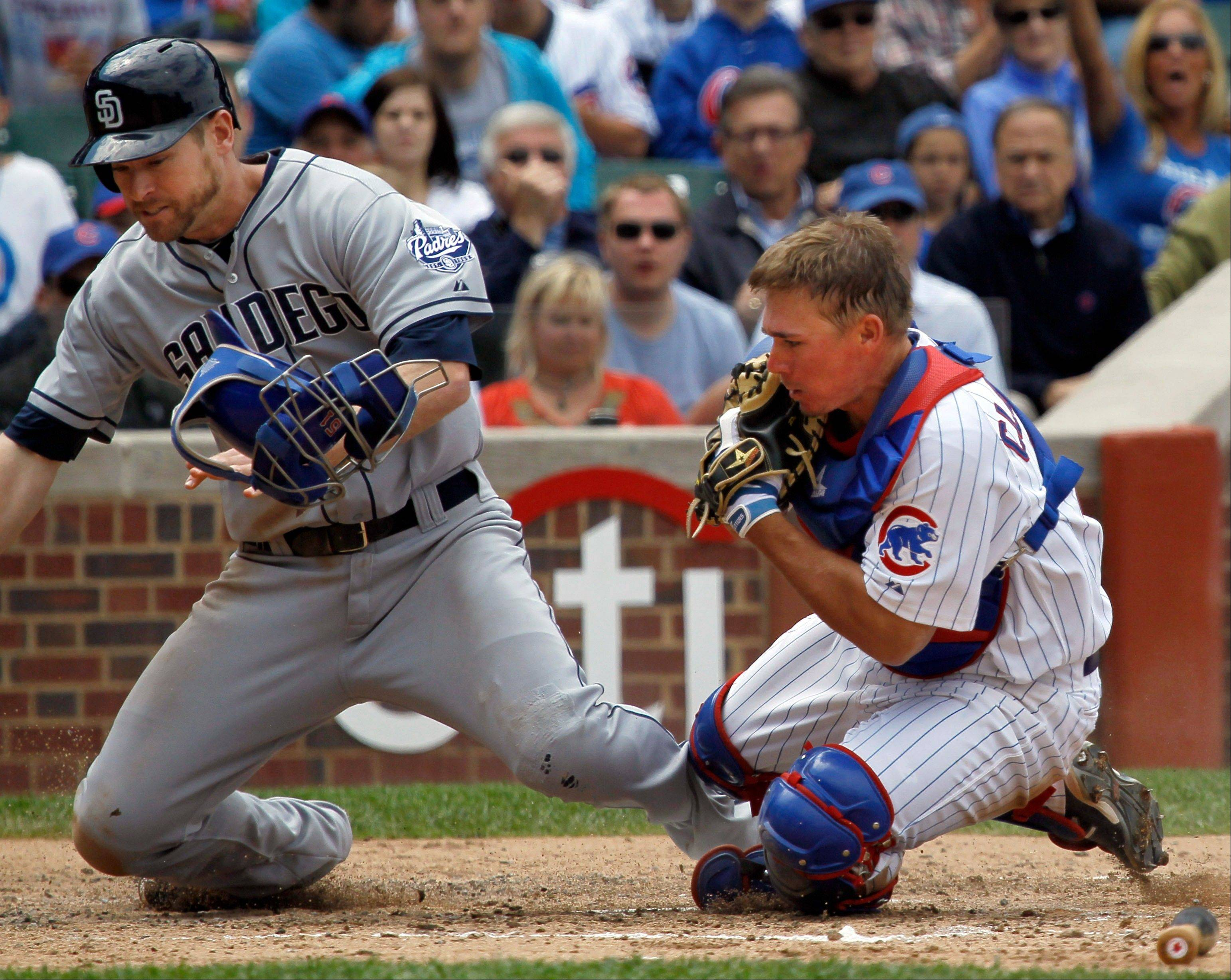 Cubs catcher Steve Clevenger holds onto the ball after tagging out the Padres' Chase Headley at the plate as he tries to score on a fielder's choice in the third inning Wednesday at Wrigley Field.