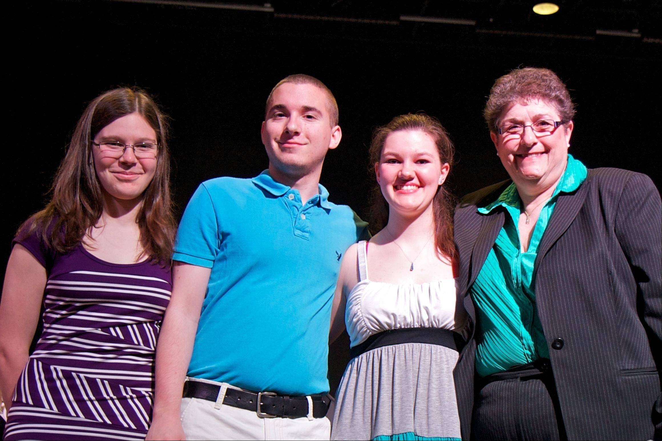 The Sun City Concert Band, with band director Donna Bressler, right, recently awarded instrumental music scholarships to three Huntley High schools, from left, Charlotte Skala, Pierce Cordel and Zoe Detlof.