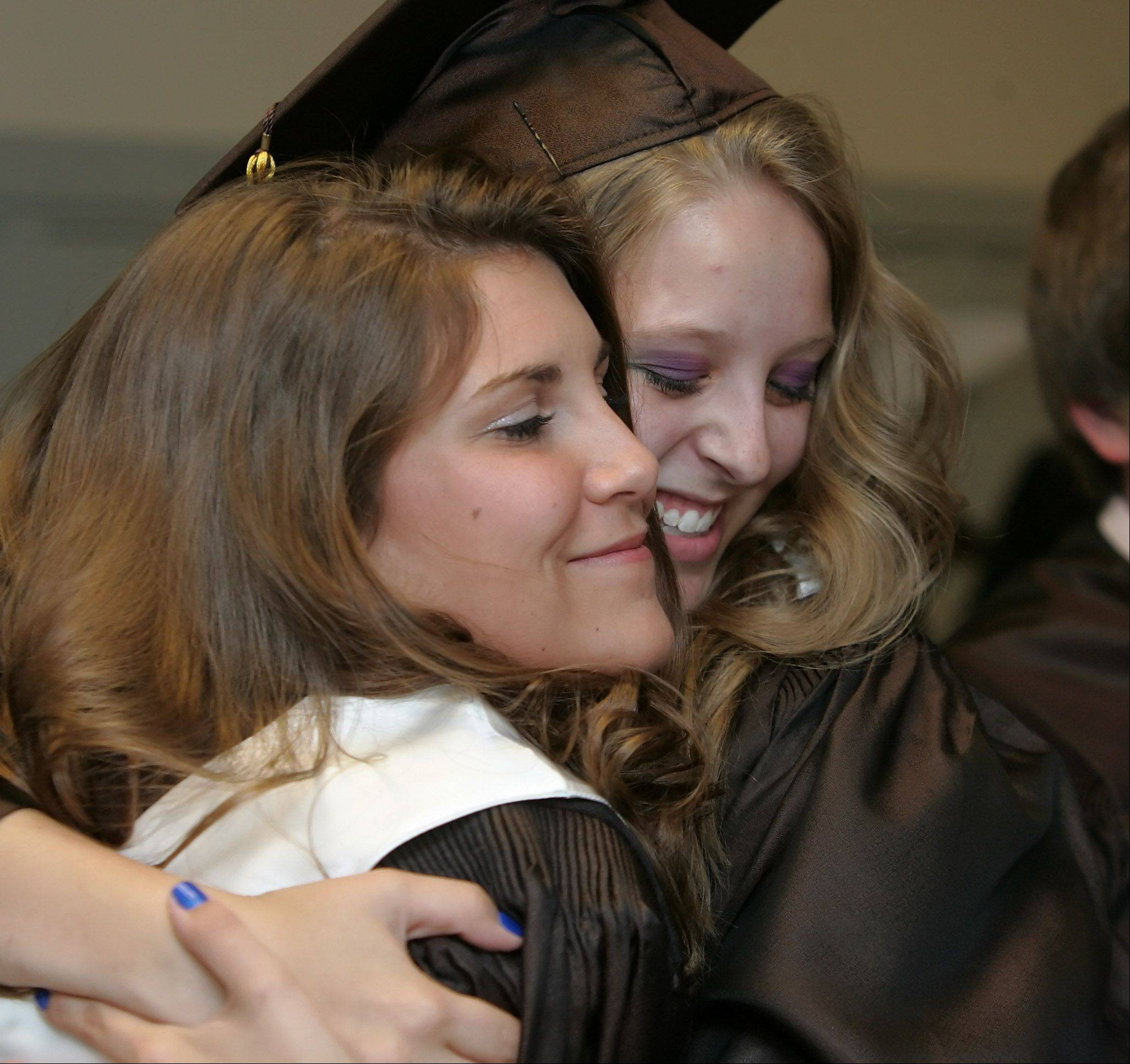 Shelby Lueders, left, embraces Nikki Roy before graduation at Carmel Catholic High School Thursday at the school in Mundelein. The 2012 class consists of 360 graduates.
