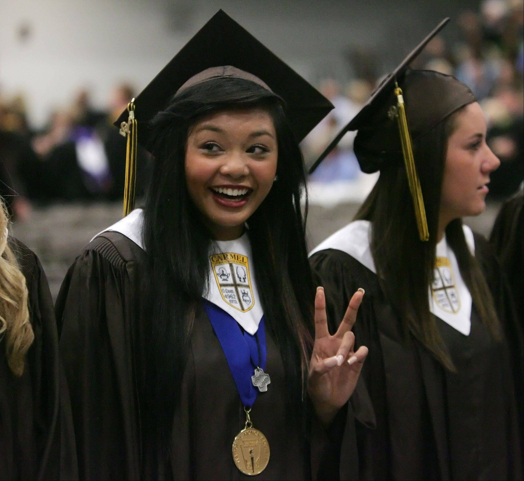 Jessica Bautista gives a victory sign to her family during graduation at Carmel Catholic High School Thursday at the school in Mundelein. The 2012 class consists of 360 graduates.