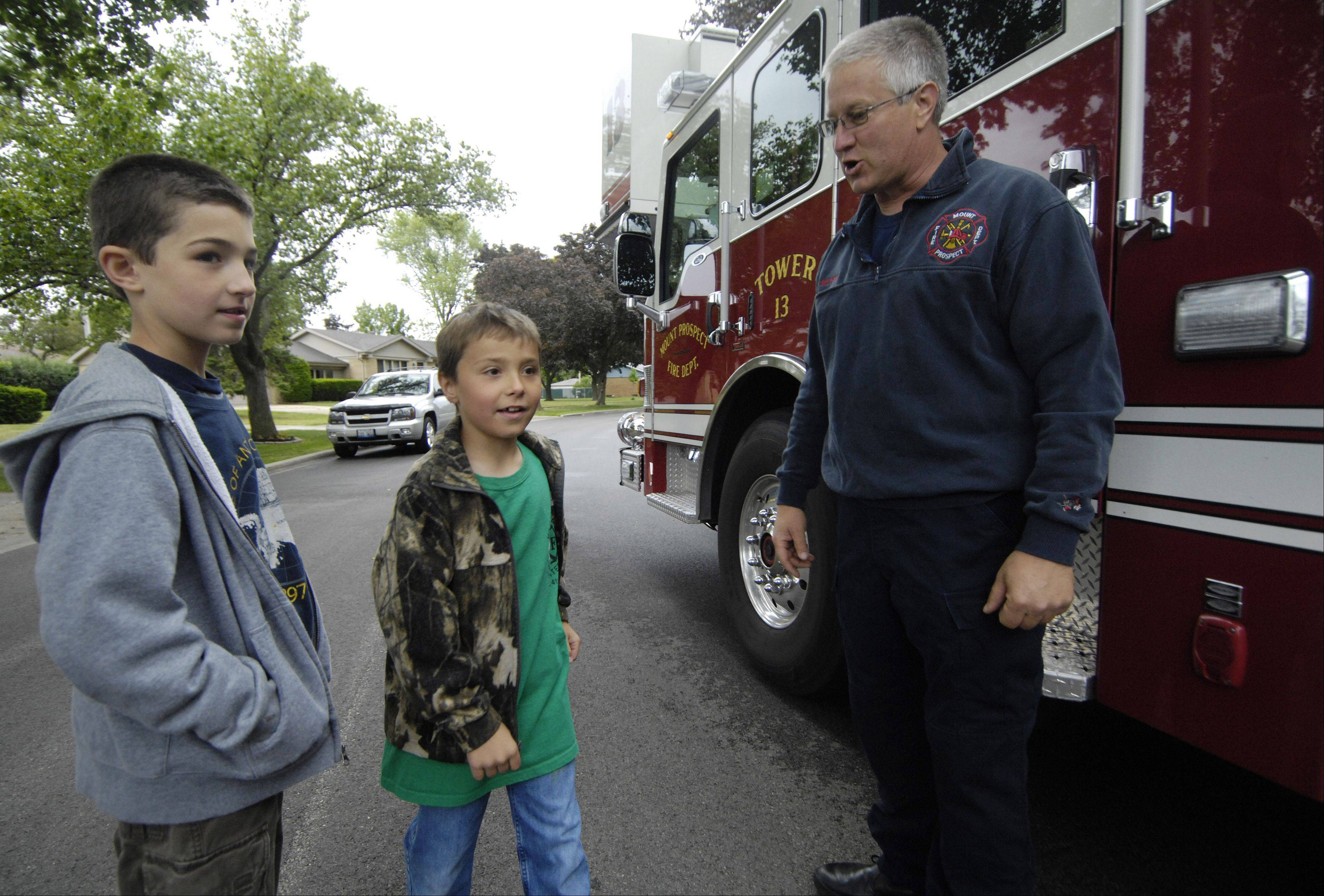 Firefighter/paramedic Pete Morris shows second-graders Carter Jedras, center, and his friend Bryce Tuchner around the engine before the boys get a ride on a fire truck to Fairview Elementary School in Mount Prospect Thursday.
