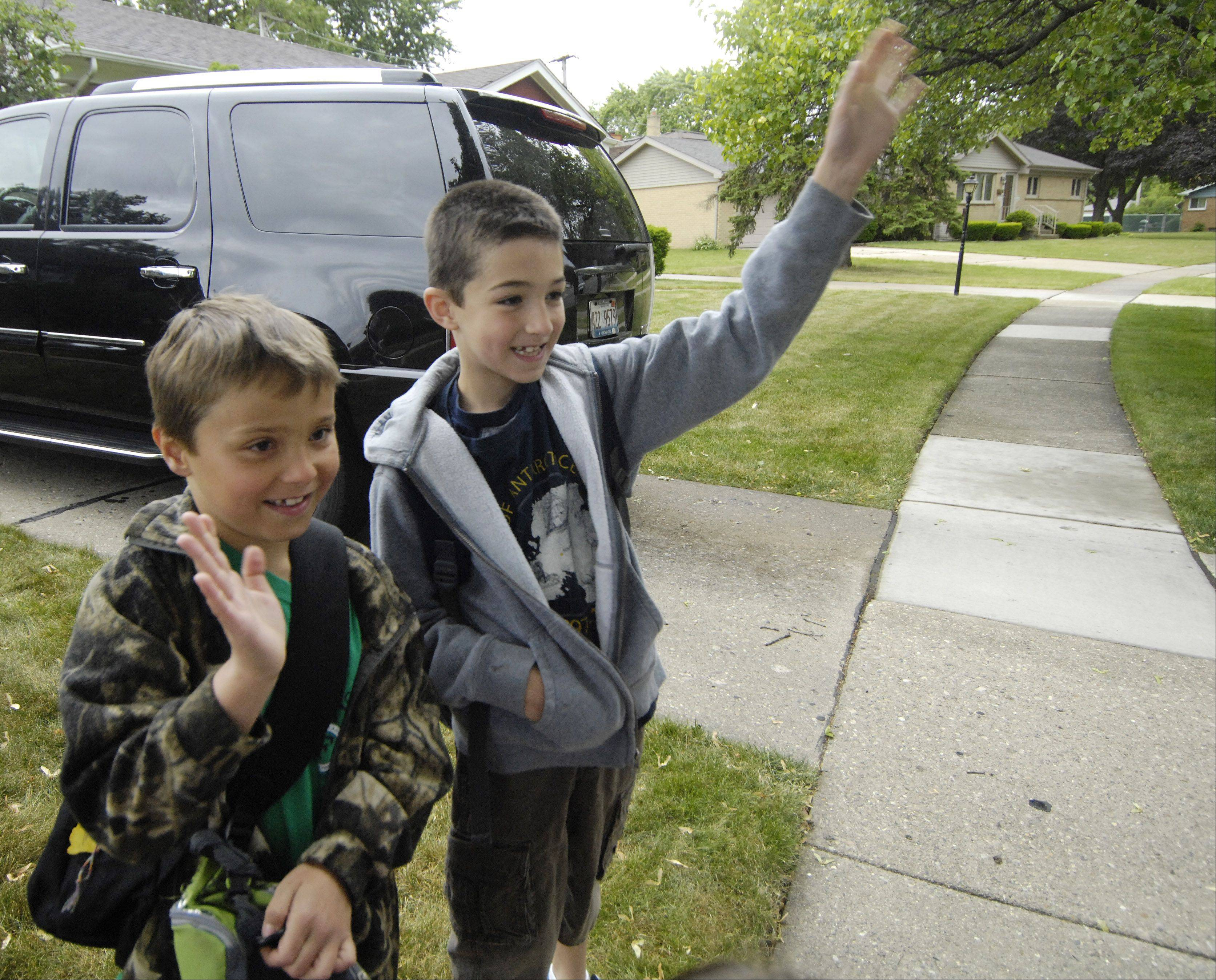 Second-graders Carter Jedras and his friend Bryce Tuchner wave as a fire engine arrives to take them to Fairview Elementary School in Mount Prospect Thursday.