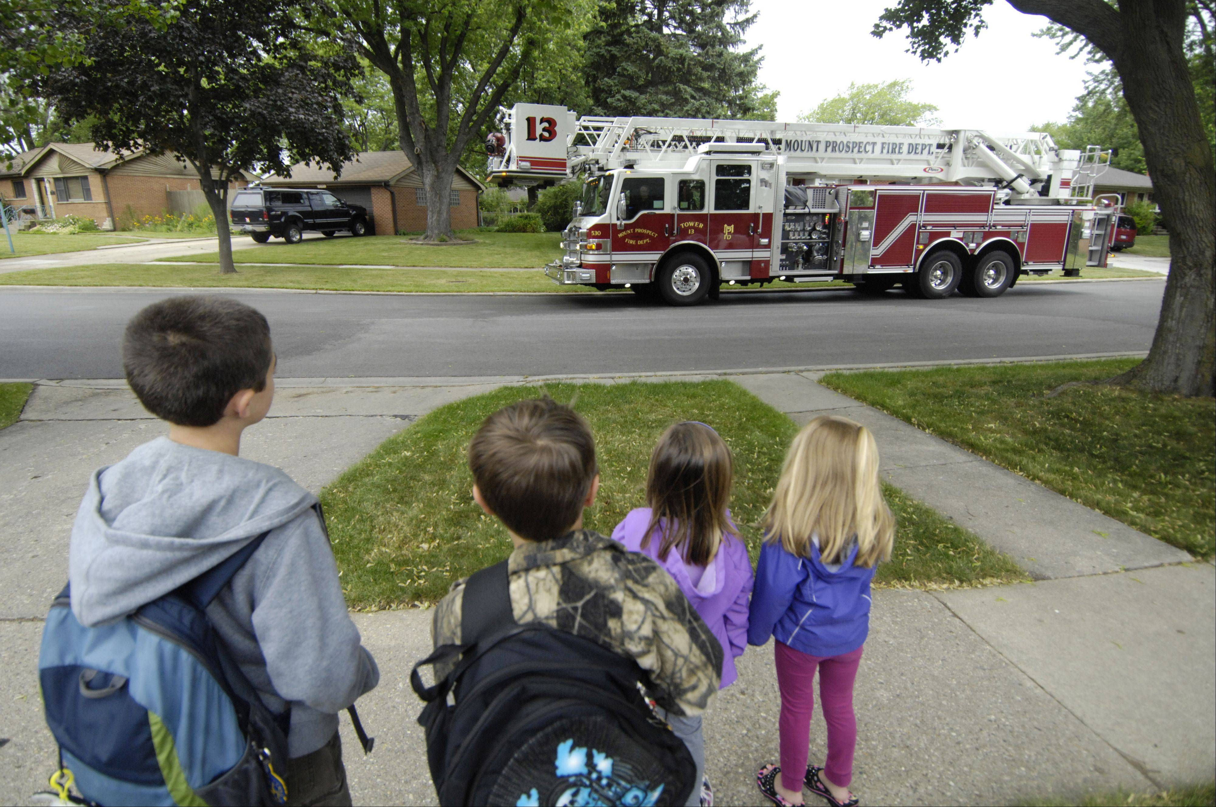 JOE LEWNARD/jlewnard@dailyherald.comSecond graders Carter Jedras, second from left, and his friend Bryce Tuchner, as well as their siblings Olivia Jedras, 4, and Mia Tuchner, 5, right, watch as a fire truck arrives to take the boys to Fairview Elementary School in Mount Prospect Thursday.