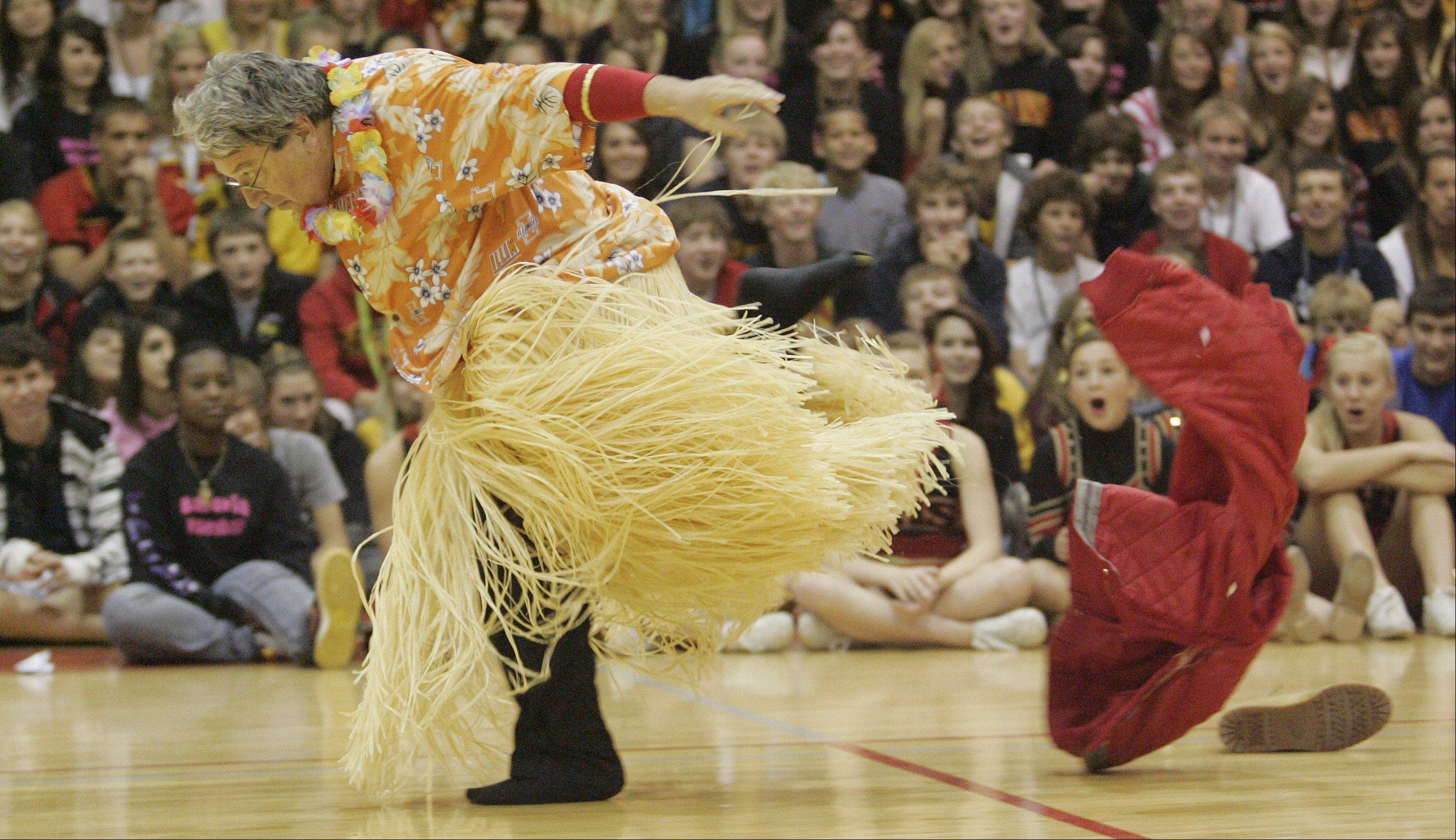 Batavia High School music teacher John Heath nearly loses his footing as he changes costumes on the run as part of his act during a homecoming pep rally at BHS.