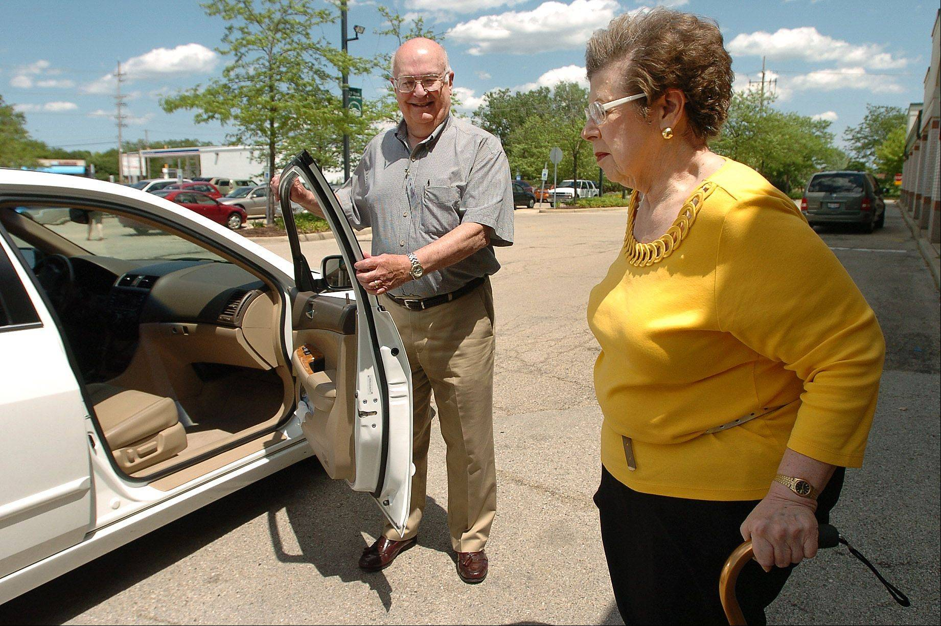 Escorted Transportation Service Northwest volunteer driver Dan Quiery holds the car door open for Marcia Cale of Arlington Heights at the Arlington Heights Senior Center.