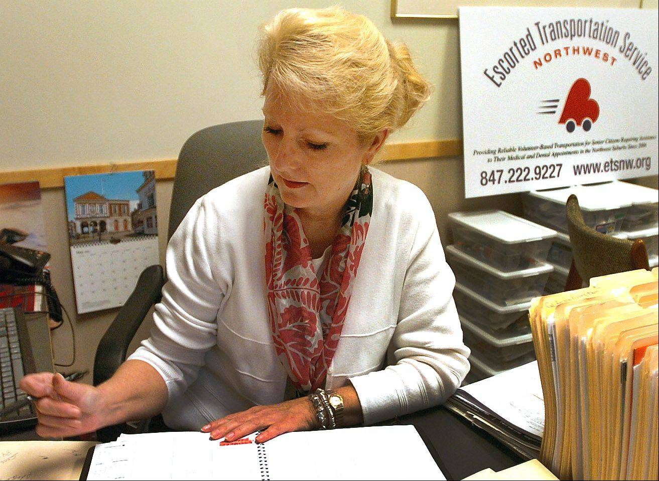 Lynndah Easterwood Lahey, executive director for Escorted Transportation Service Northwest, works on a schedule in her office at the Arlington Heights Senior Center.