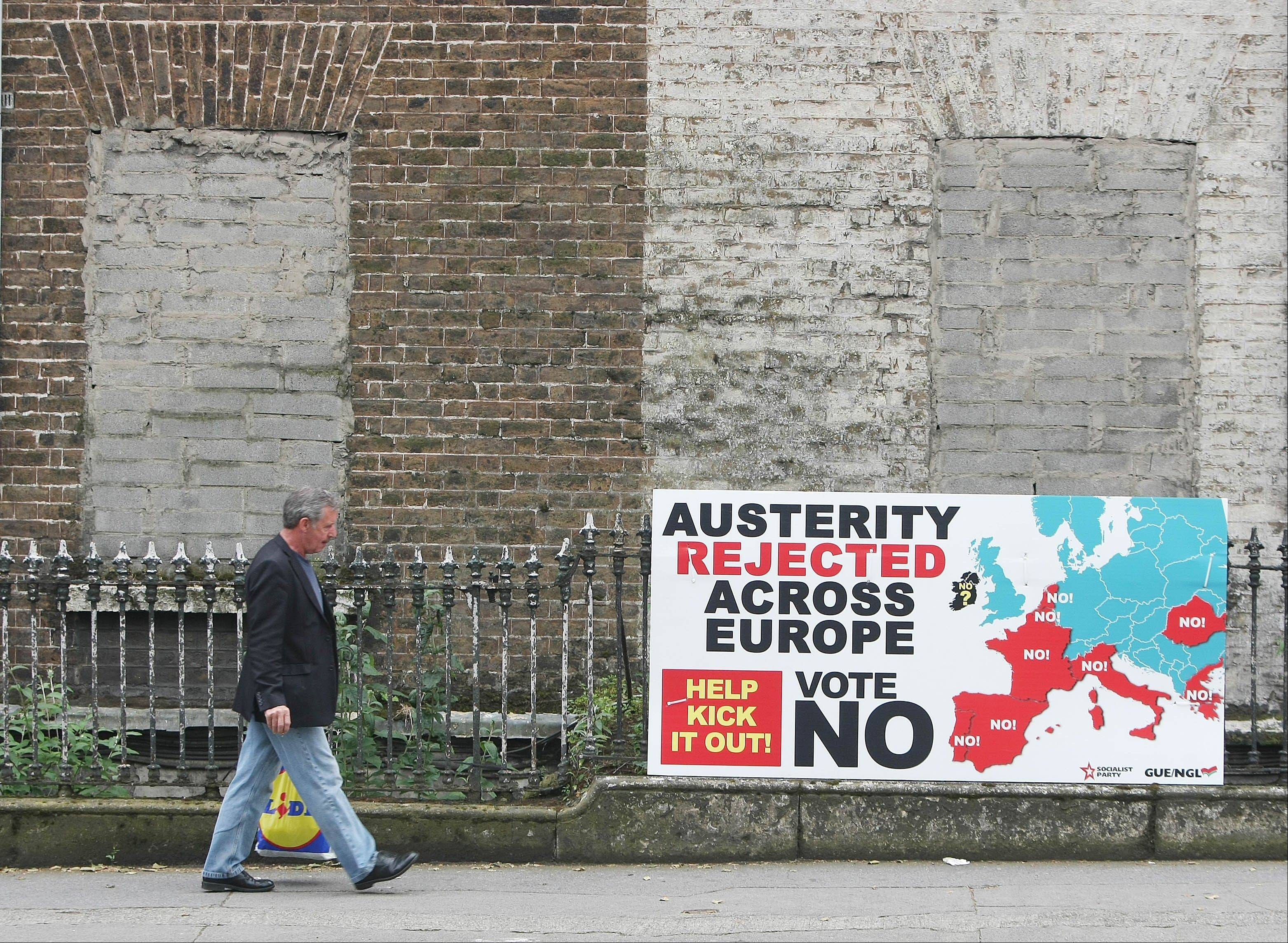 A man walks past a sign against the European Fiscal Treaty in Dublin Wednesday May 30, 2012 ahead of Thursdays referendum. Ireland is the only country in Europe holding a referendum on the treaty as it is obliged to put major EU reforms to the public test according to the Constitution.
