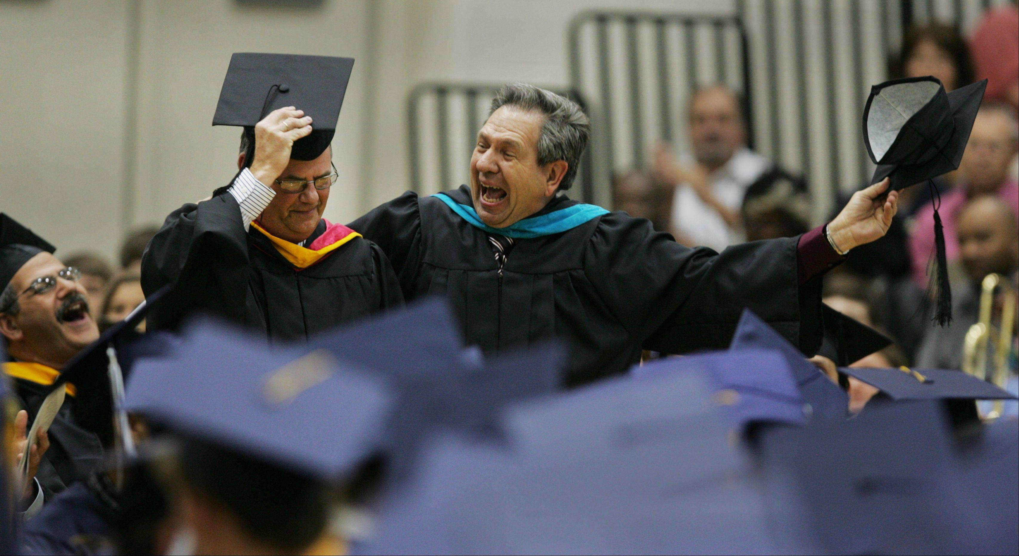 Retiring Lisle High School teachers Mike Coit, left, and Ken Jakalski, right, are applauded for their service, during graduation ceremonies. One hundred forty-five Lisle students graduated.