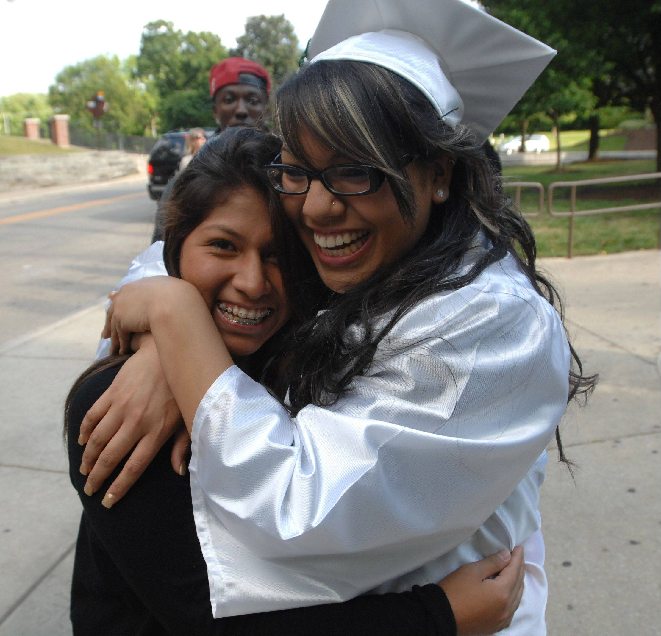 Lucia Flores, left, and Mariah Flores, both of Glendale Heights hug during the Glenbard West graduation in Glen Ellyn Friday. They are friends but not sisters despite the same last name.
