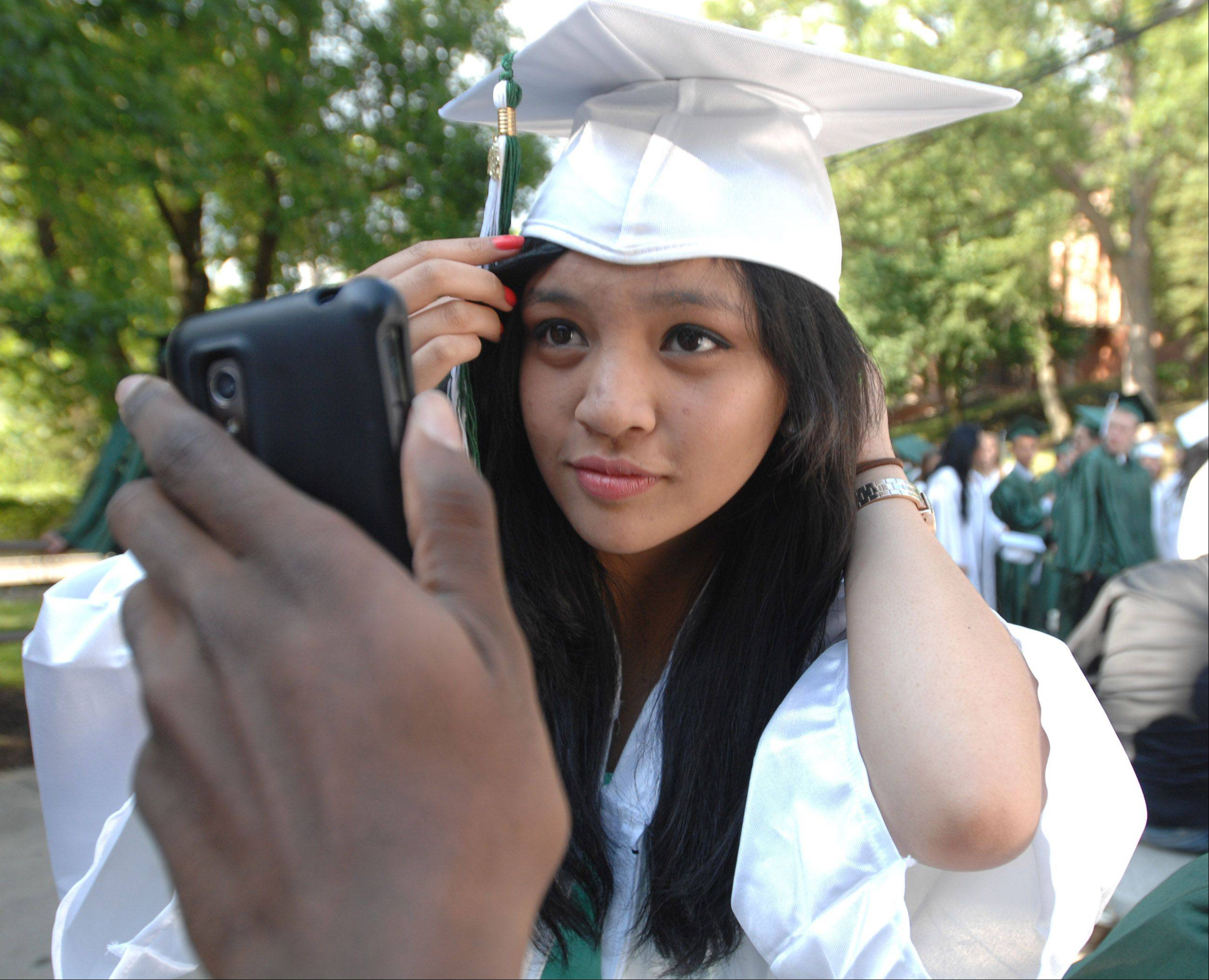Nicole Celestino of Glendale Heights fixes her hair in a reflection from a cell phone just before the start of the Glenbard West graduation in Glen Ellyn Friday.