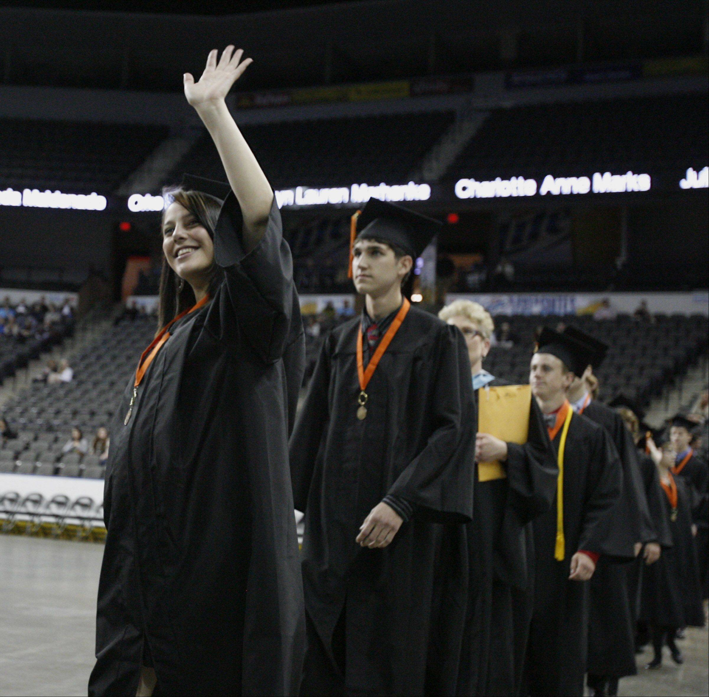 Sydney Hancock waves to friends while walking into Libertyville High School graduation ceremony on Friday, June 1 at the Sears Centre in Hoffman Estates.