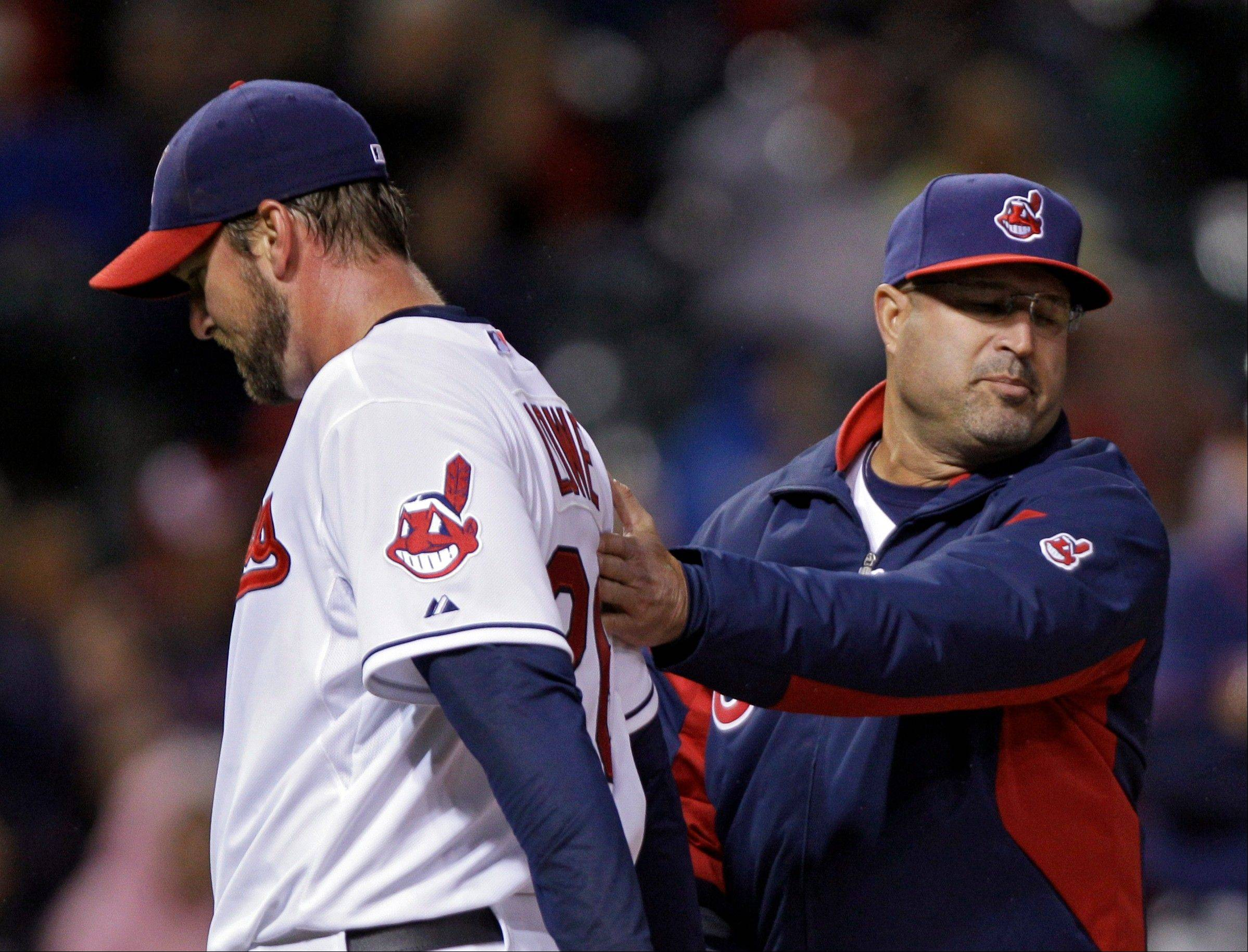 Cleveland Indians manager Manny Acta gives starting pitcher Derek Lowe a pat on the back as Acta brings in a reliever Friday during the seventh inning against the Minnesota Twins in Cleveland.