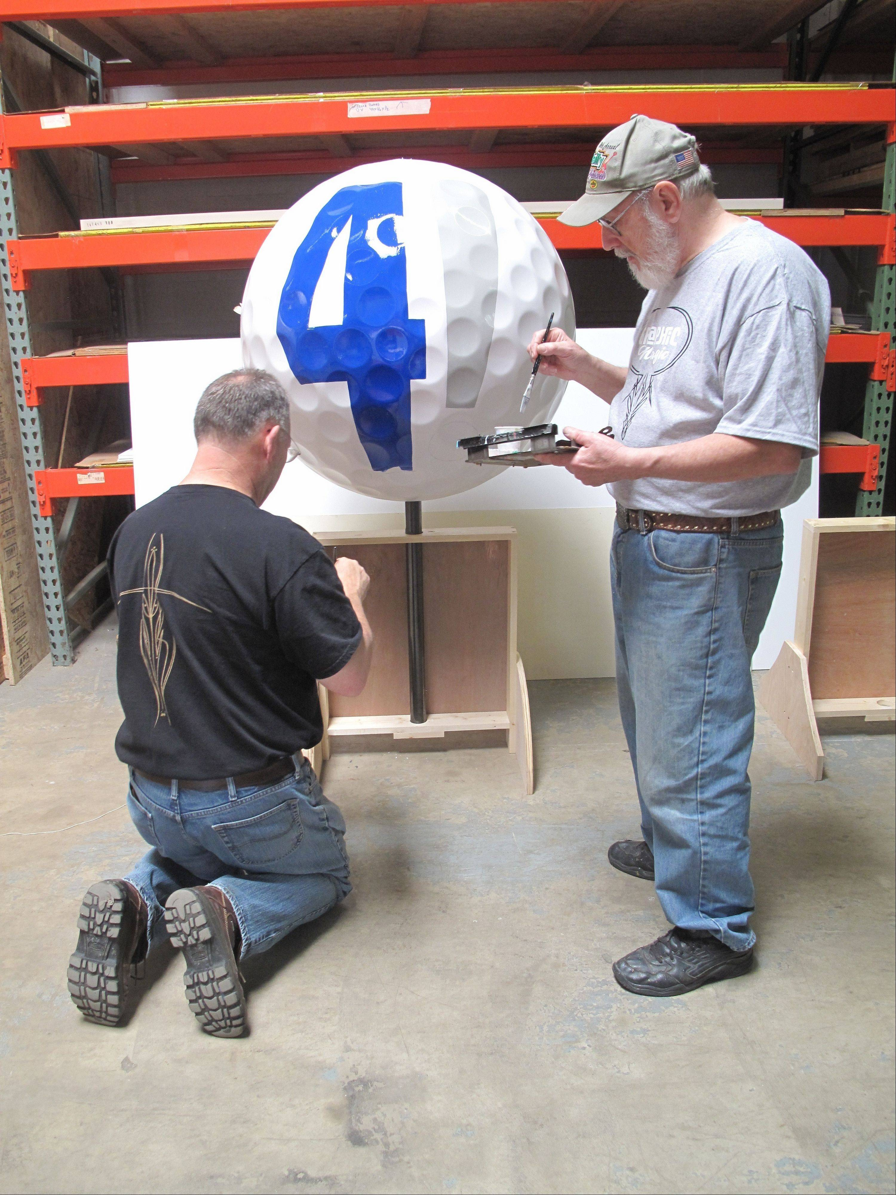 "Bob Behounek and Ron Jelinek of Chicago BrushMasters paint a giant golf ball Saturday for the ""Tartan Art on the Avenue"" exhibit that will accompany the Ryder Cup when the international golf event takes place this fall at Medinah Country Club."
