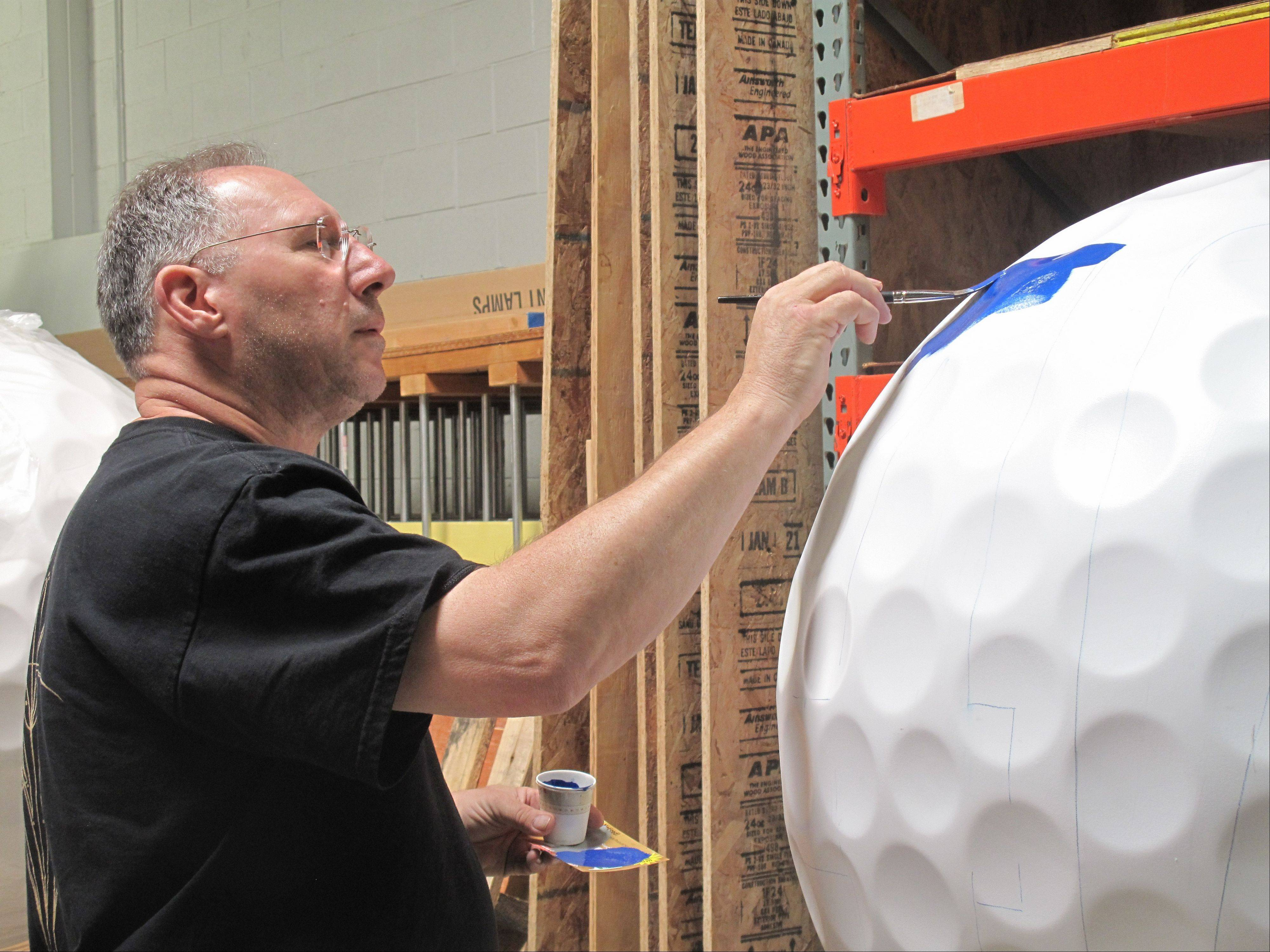 Bob Behounek of Chicago BrushMasters, a group of artisan sign painters that raises money for Ronald McDonald House Charities, begins painting a giant golf ball to be used in an art exhibit coinciding with the September arrival of the Ryder Cup international golf tournament to Medinah Country Club.