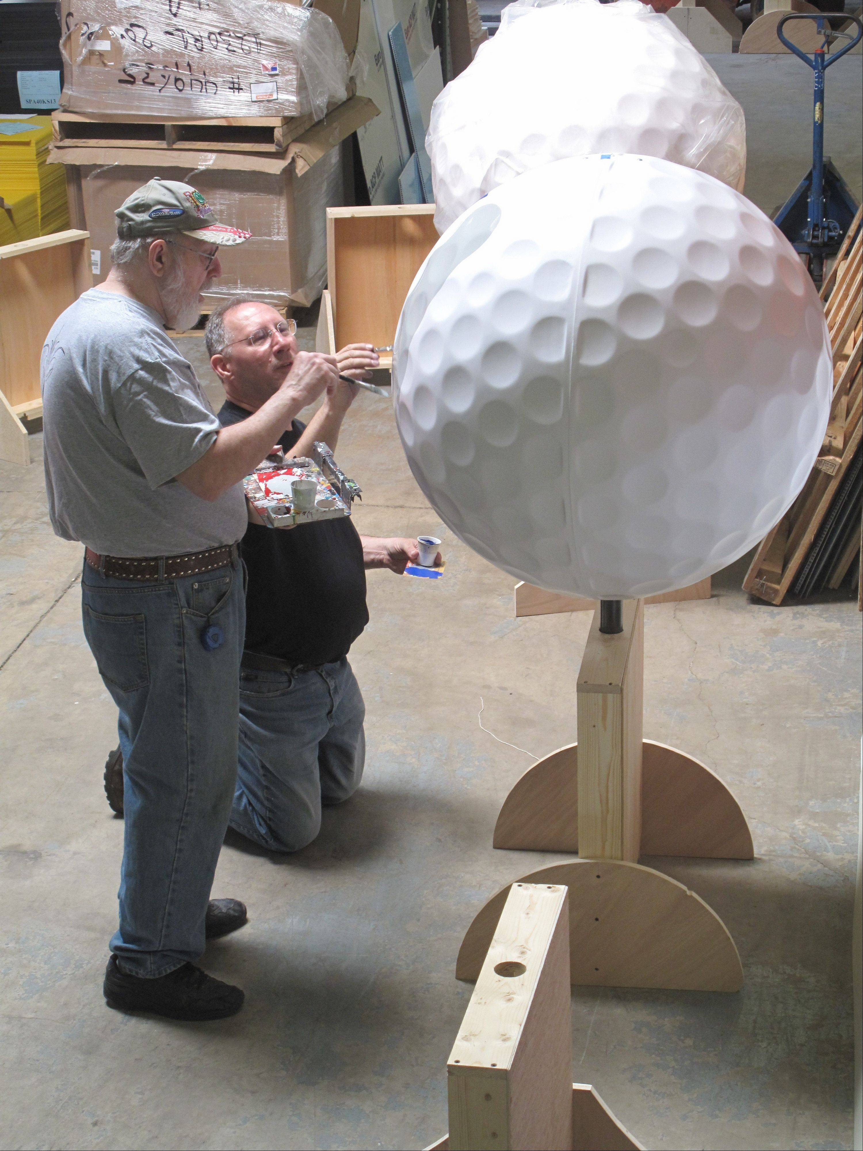 "Ron Jelinek and Bob Behounek team up to paint ""4!"" on a giant golf ball to be used in the ""Tartan Art on the Avenue"" exhibit to coincide with the Ryder Cup at Medinah Country Club this fall. The ball's design plays on the warning of ""fore"" yelled by golfers who have hit errant shots."