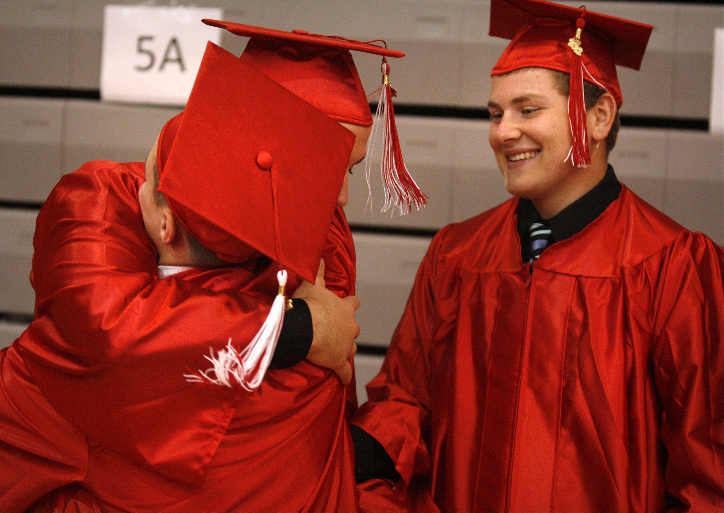 Grant High School's Kole Harvey gets a hug from Benjamin Soumer, after hugging graduating classmate Anthony DiCosola, right, at the school's graduation on Saturday, June 2 in Fox Lake.