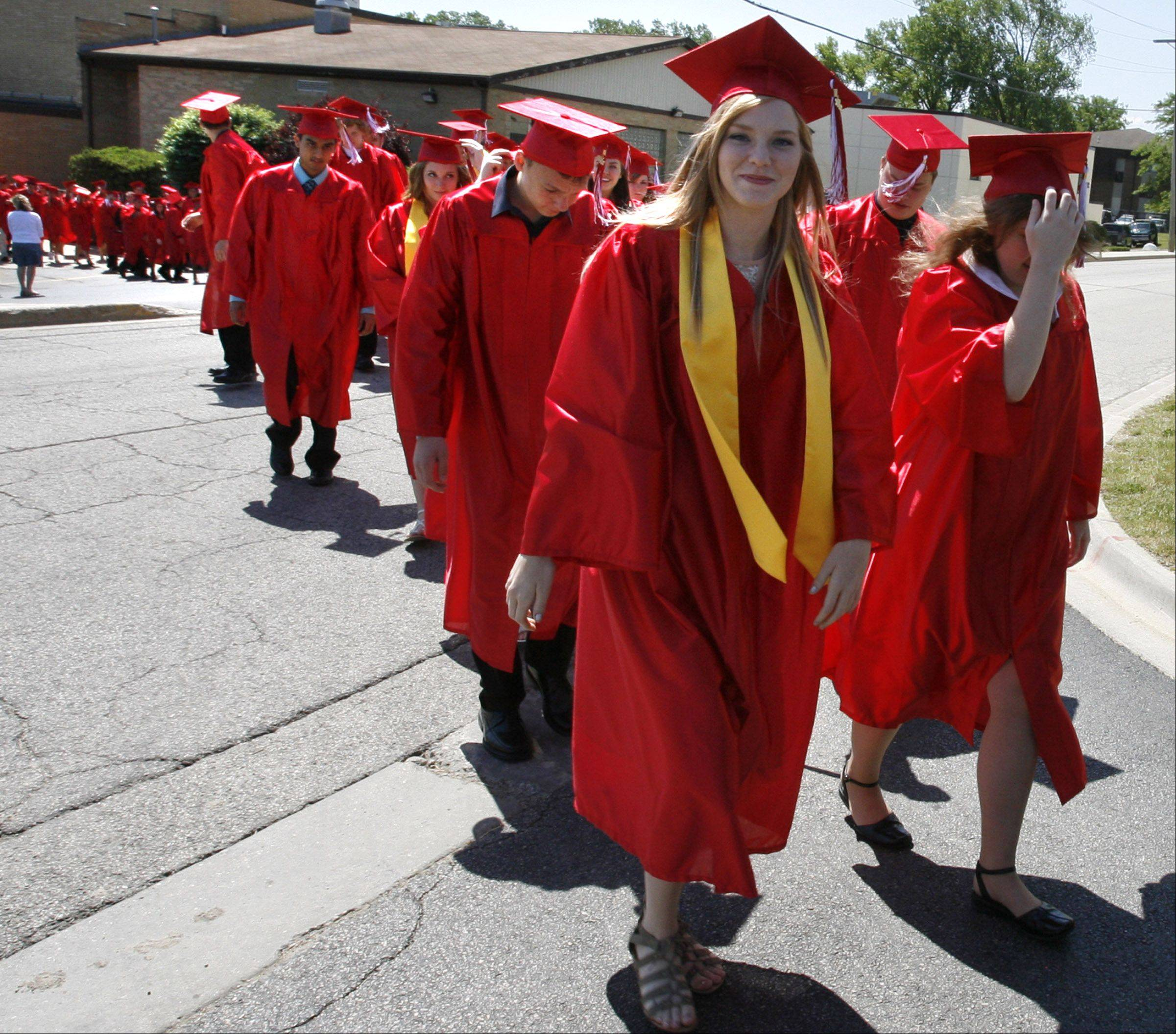 LoriBeth Achtor, left, and Kayla Boyd lead Grant High School graduates from across the street to the gym for the school's graduation on Saturday, June 2 in Fox Lake.