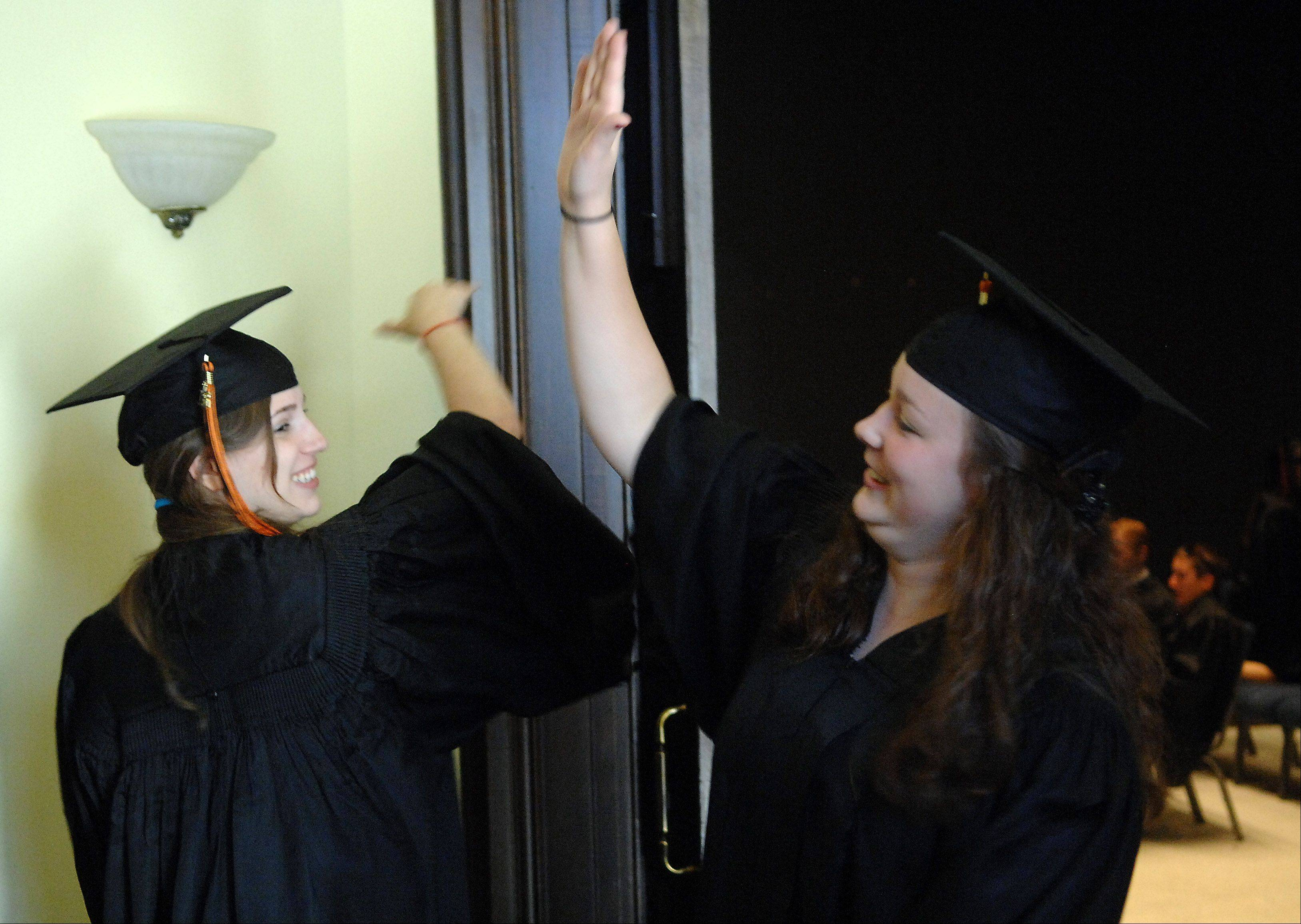 Hana Goodman of Woodstock, left, and Larisa Sica of Campton Hills high five before the start of Elgin Academy's graduation ceremony Saturday.