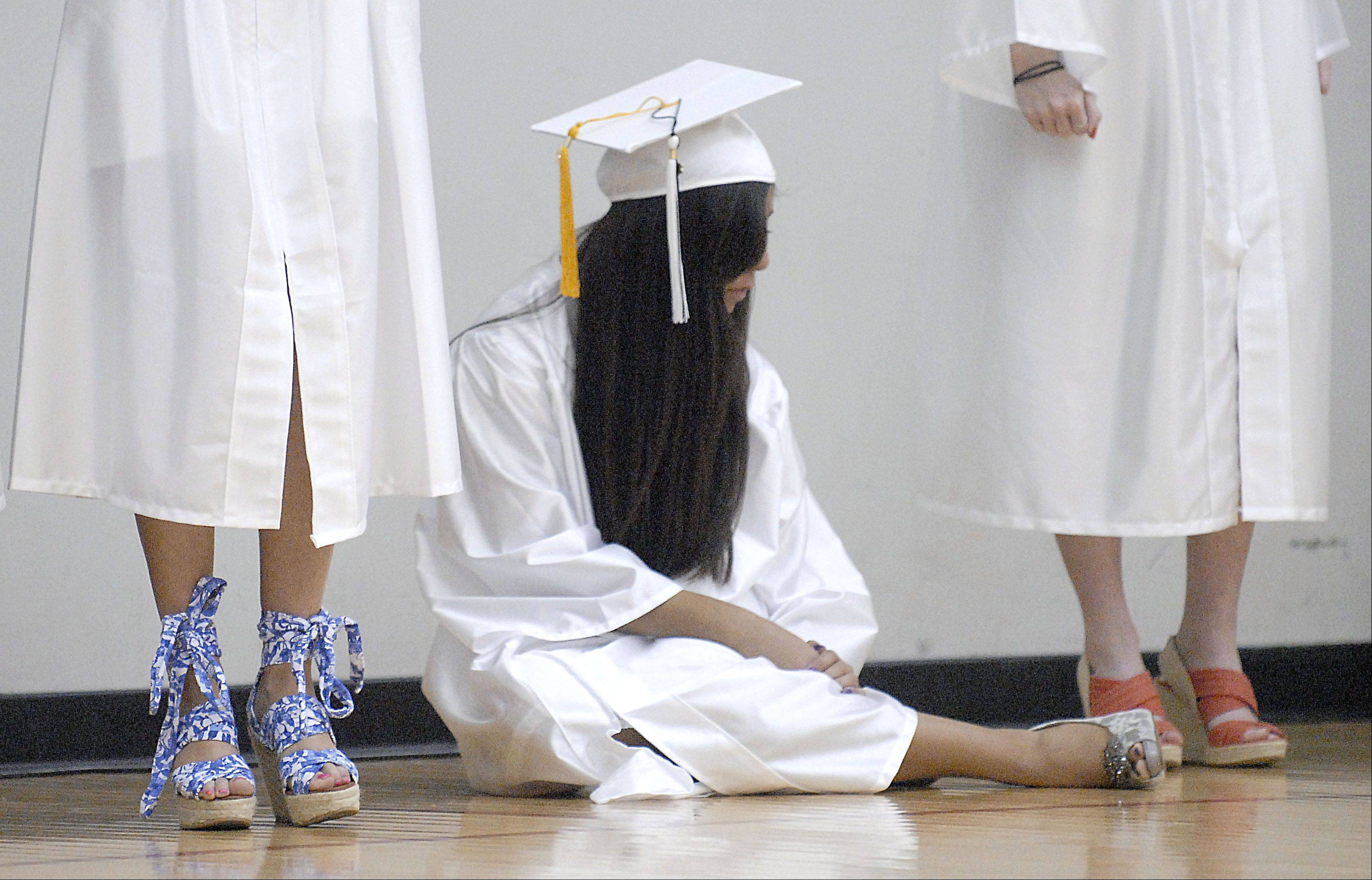 Marissa Villafuerte sits on the floor waiting for Kaneland High School's commencement ceremony to begin at the NIU Convocation Center in DeKalb on Saturday, June 2.