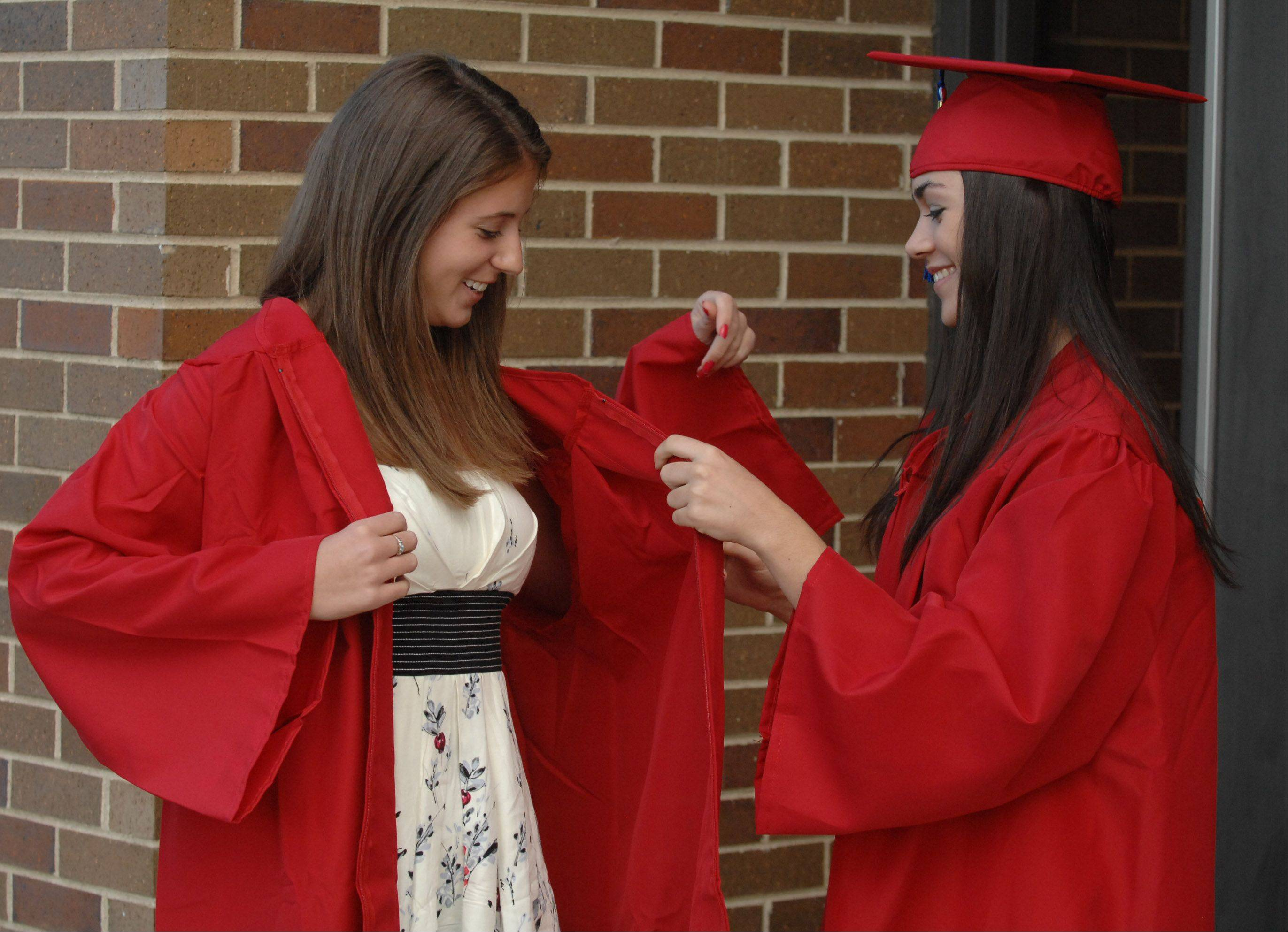 Patrica Buehler, left, and Michelle Tykvart help each other with their gowns before the Glenbard South graduation in Glen Ellyn Friday.