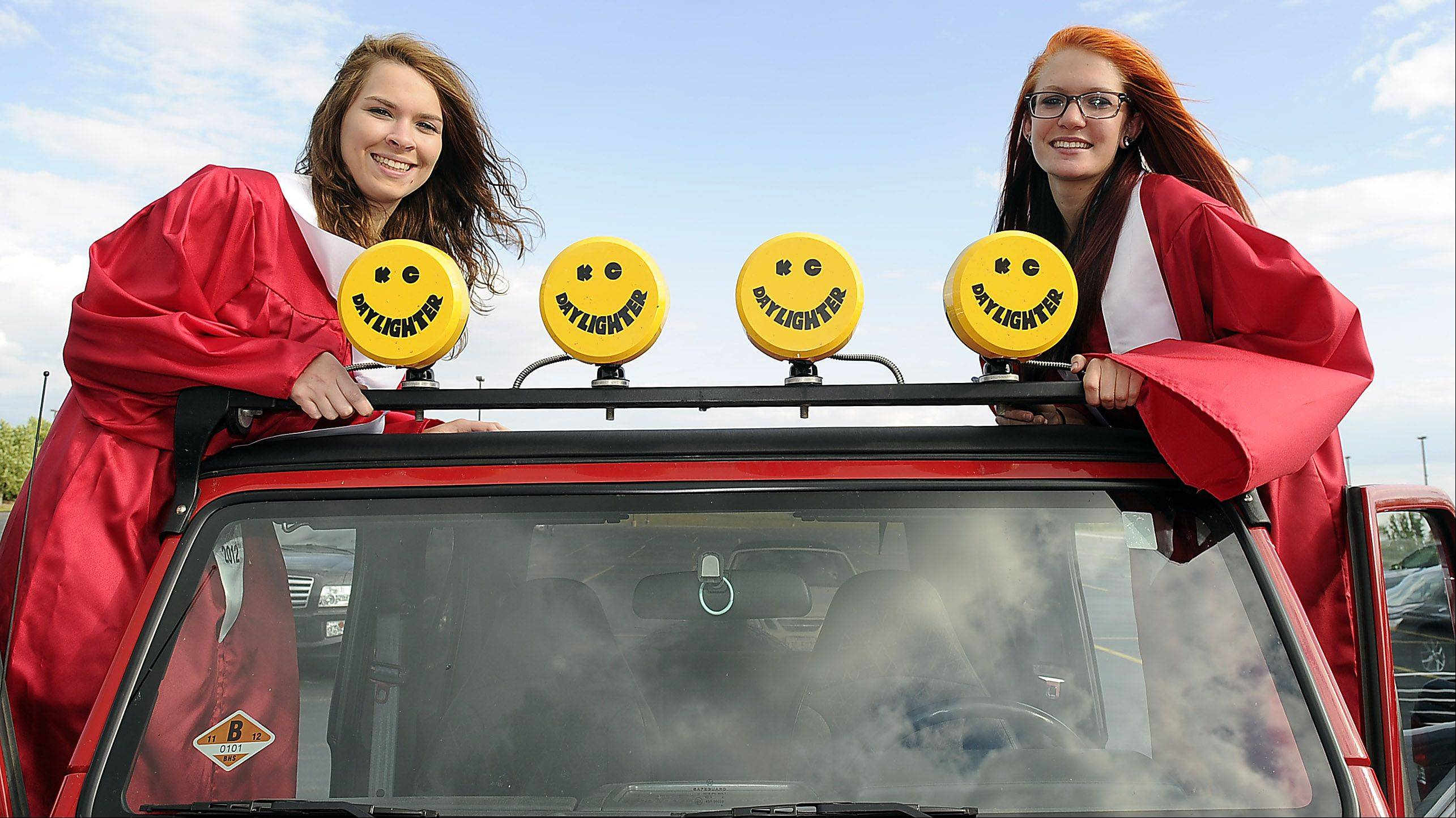 Barrington High School soon-to-be graduates Emily Clampitt and Elisabeth Paladino have a little fun in the parking lot before their graduation at Willow Creek Community Church on Friday.