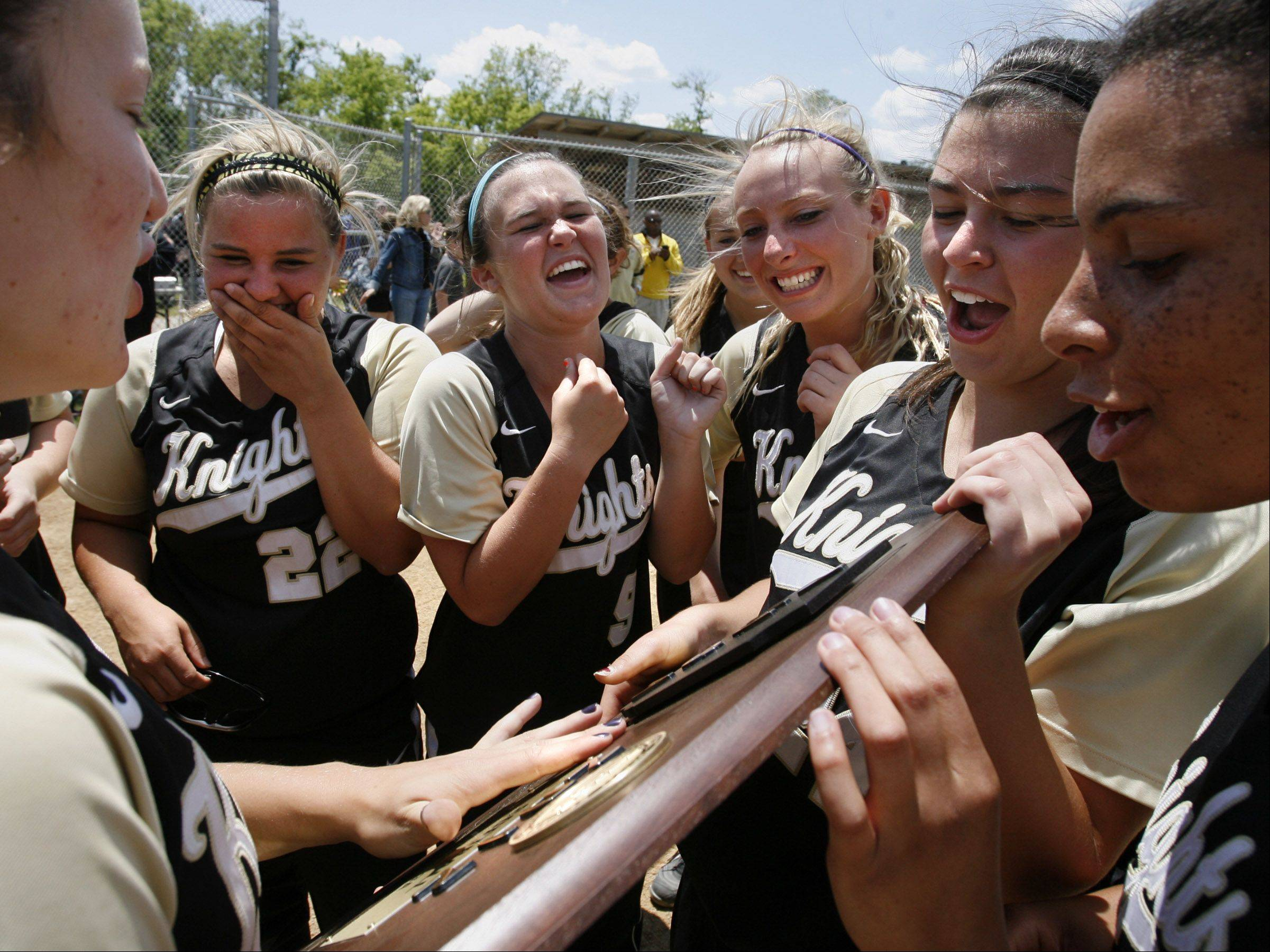 Grayslake North's softball team, including pitcher Kristina Gandy, second from right, Kelsey Borders, second from left (22), and Jessica Davis, center (9), celebrate and touch the Class 3A Lakes softball sectional final plaque after winning against Prairie Ridge in Lake Villa on Saturday.