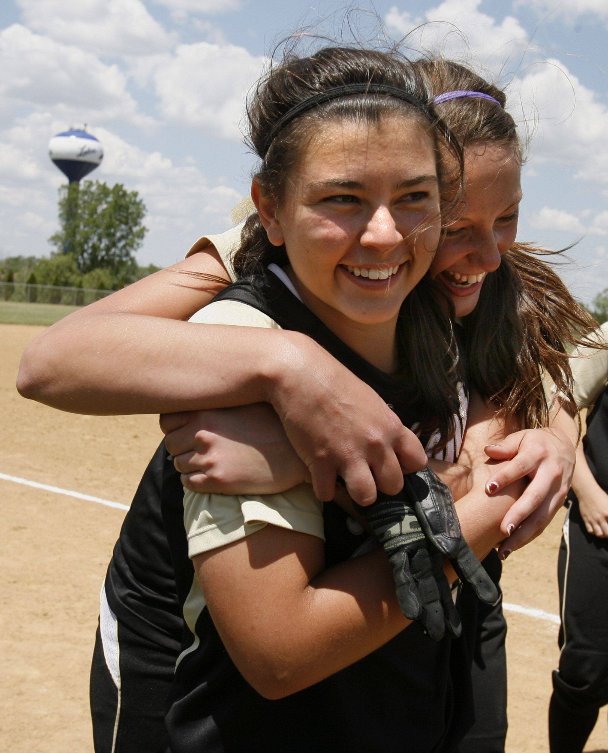 Grayslake North pitcher Kristina Gandy gets a hug from Christina Freese after winning the Class 3A Lakes softball sectional final against Prairie Ridge in Lake Villa on Saturday.