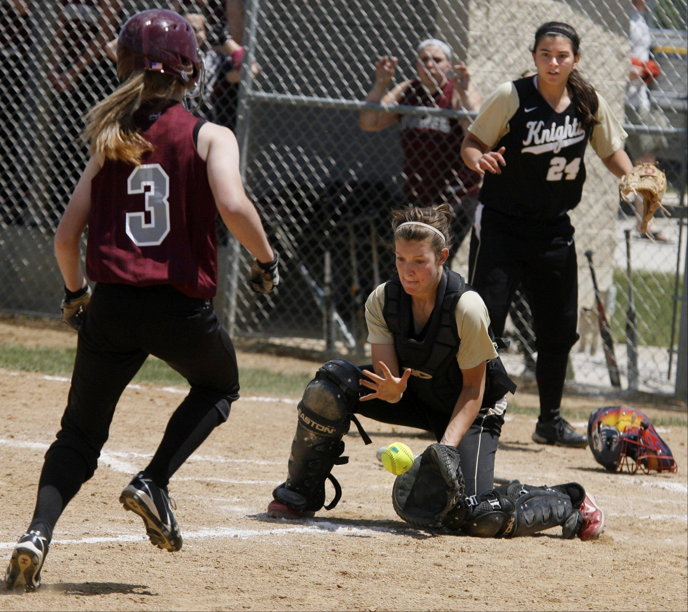 Grayslake North catcher Brooke Tracy catches a throw to the plate backed-up by pitcher Kristina Gandy as Prairie Ridge's Erin Wing is tagged out in the Class 3A Lakes softball sectional final in Lake Villa on Saturday.