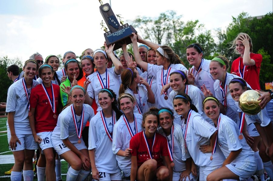 The St. Viator girls soccer team hoists its third-place trophy after defeating Normal University in the girls soccer Class 2A tournament.