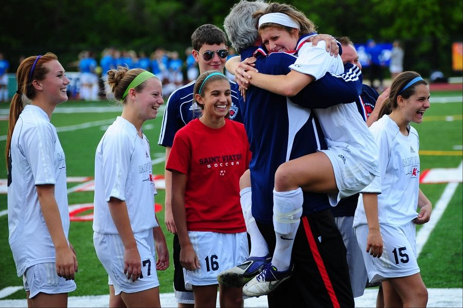 St. Viator girls soccer coach Mike Taylor hugs his players as they step down from the medals podium after winning third place in the girls soccer Class 2A tournament.