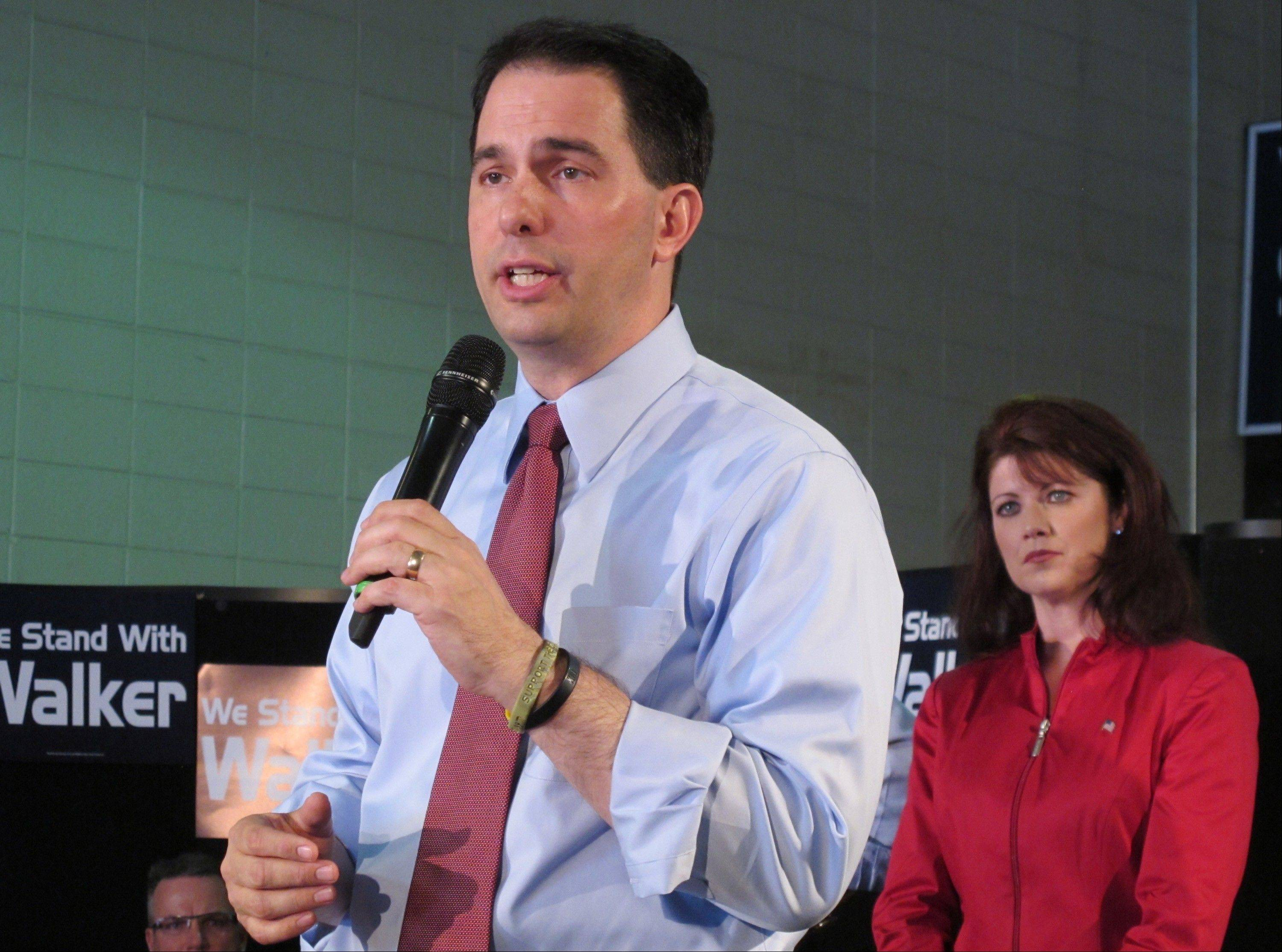 Wisconsin Gov. Scott Walker addresses supporters last month in Waukesha as Lt. Gov. Rebecca Kleefisch listens. Both face recall elections Tuesday on separate ballots.