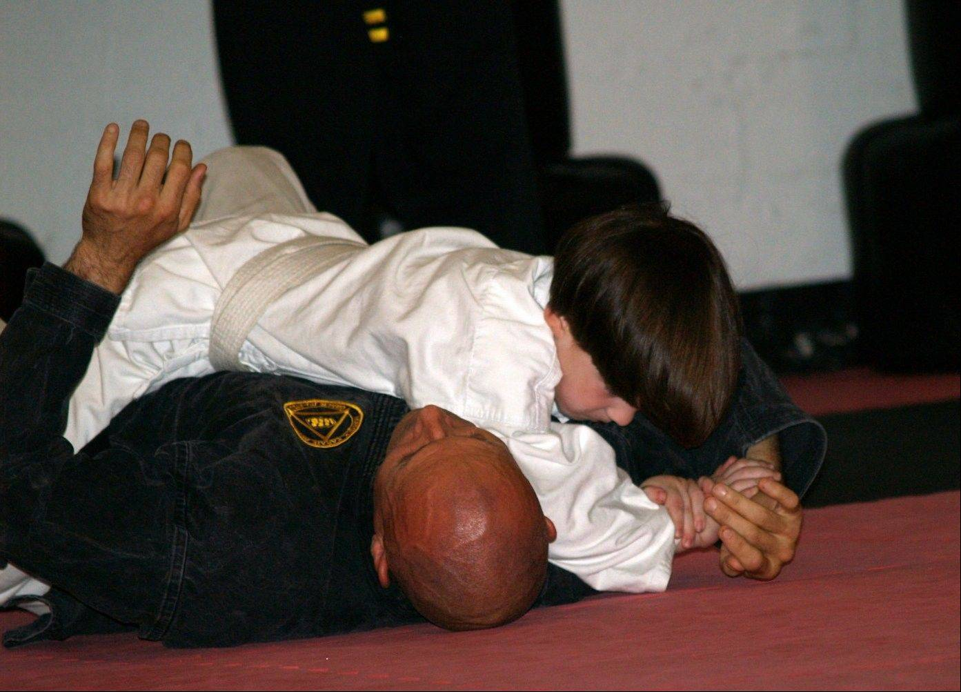 This June 2010 photo provided by Lisa Suhay shows her son Quin Suhay, now 8, tackling Bill Odom, owner of Norfolk Karate Academy in Norfolk, Va., as part of a bullyproofing class that combines jujitsu _ defensive moves only, no punching or kicking _ with verbal strategies. Other types of bullyproofing programs, including guides for parents and regular classroom curricula, seek to make kids l